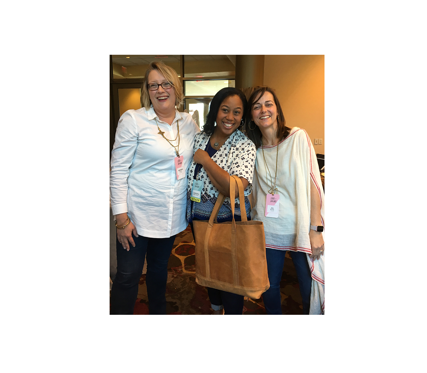 Karama Executive Directors Kristine Cordts and Jill Morley pose with Chrystal Evans Hurst, best selling author of 'Kingdom Woman', during a session break with the beloved large Addis Tote in Camel.