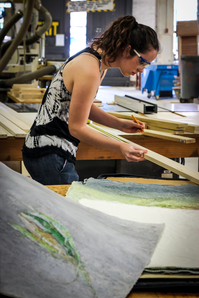 Shelby Prindaville and her artwork, as she works in the woodshop. Photo by Paige Jarreau.
