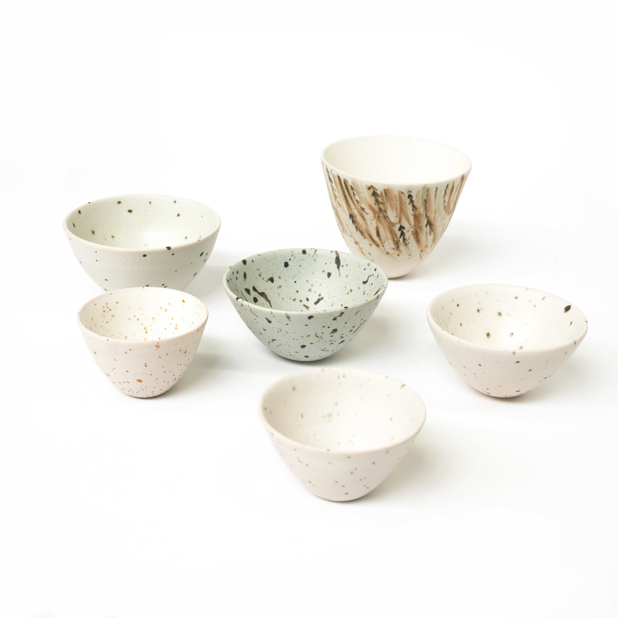 Matte glazed thrown and handpainted stoneware feather and eggshell bowls