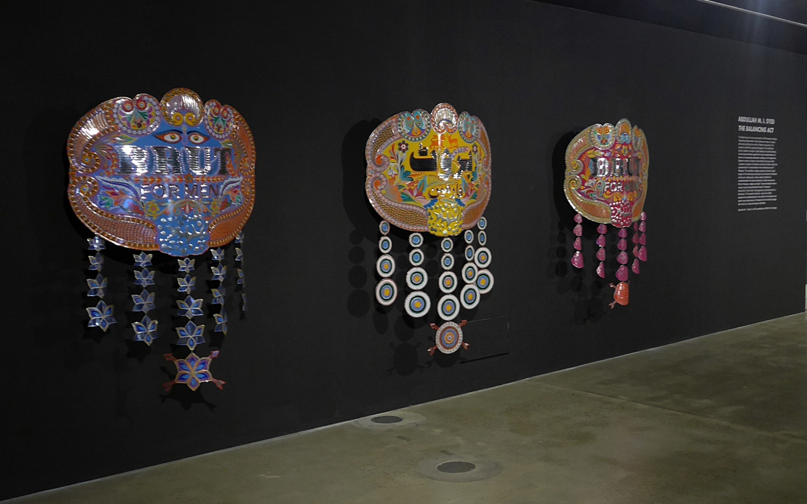 Brut for Men : Target, 2013, chamk patti (Hand-Cut Vinyl sticker ornamentation), hand beaten metal medallion, wood and stainless steel. 150 x 117 x 15 cm. In collaboration with Pakistani Truck Art craftspeople (Sahid Bhai's and his Karkhana Team, Karachi). Installation view: 4A Centre for Contemapoary Asian Art, Sydney