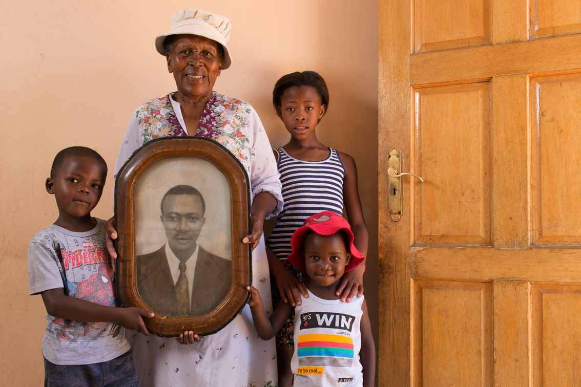 Mrs. Dibe, holding the portrait of her late husband, Bishop Cecil Shuping Dibe. Adelina is surrounded by her grandchildren Thuto (6), Ntombizodwa (11) and Boichoko (3).