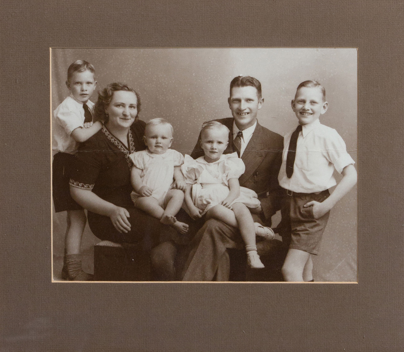 Barbara with her parents and her brothers (1948). Barbara sits on her father's lap. Mom holds Freddy, the youngest one. Ralph stands on mom's left and next to her husband, their oldest boy Patrick.
