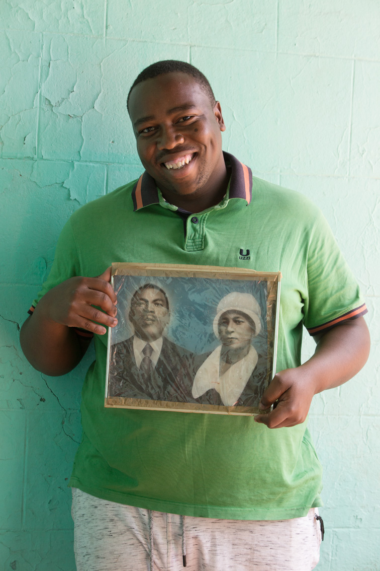 Mr. Samuel Magengenene is Mr. Pudumo's nephew. Named after the gentleman in the portrait, Samuel holds a plastic-wrapped, hand-coloured black-and-white photograph of his great-grandparents, Samuel Tlale Nkone and Rosta Nobelungu Nkone. Samuel was a prison warden, Rosta a domestic worker. Bochabela/Bloemfontein (Free State, RSA) 2018.