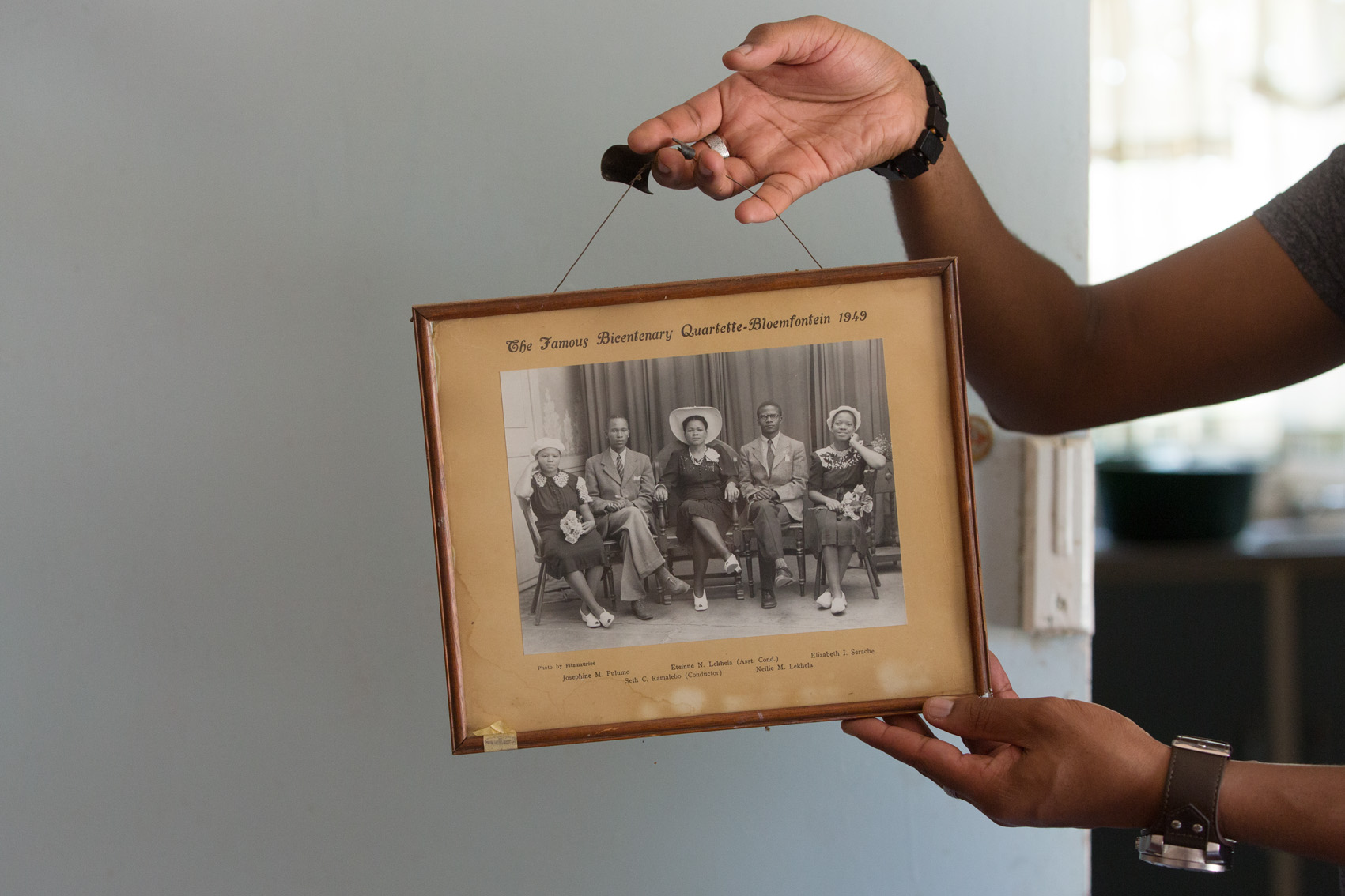 """Mr. Pudumo holds a framed black-and-white portrait of """"The Famous Bicentenary Quartette"""" dated 1949. On the left, his great-aunt Josephine M. Pulumo (sic)."""