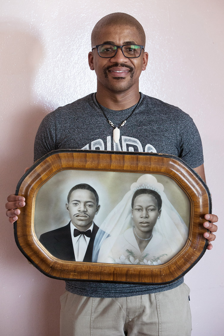 Mr. Pudumo, holding the framed, hand-coloured black-and-white wedding portrait of his grandparents.
