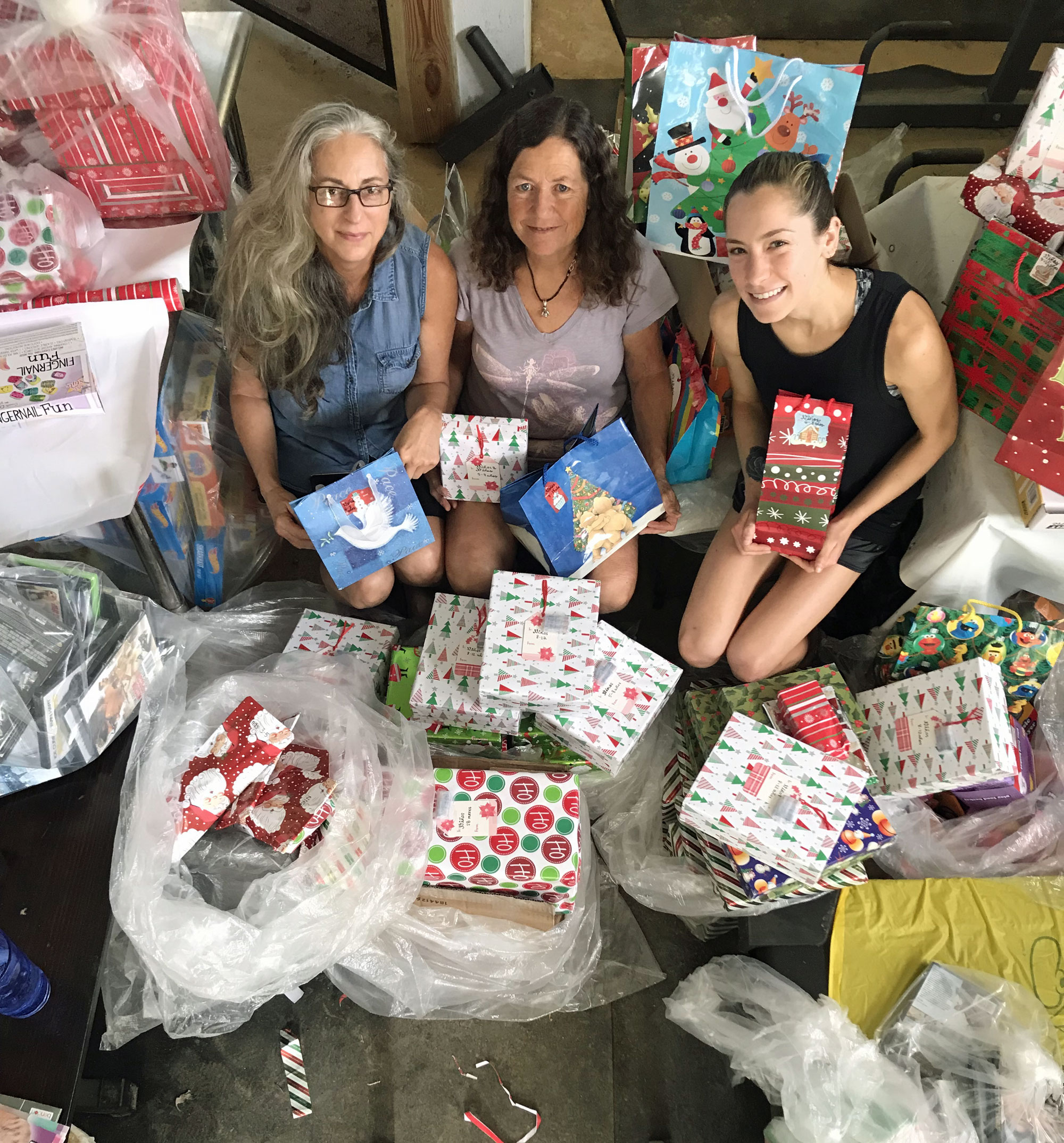 Renée, Laurie Michaels and Melina Devoney posing during their present wrapping