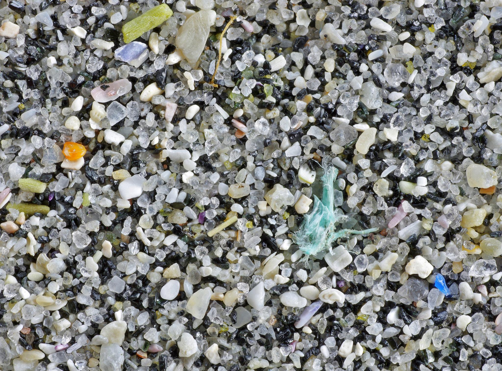 Et nærbilde av strandsand, avslører små biter av plast.