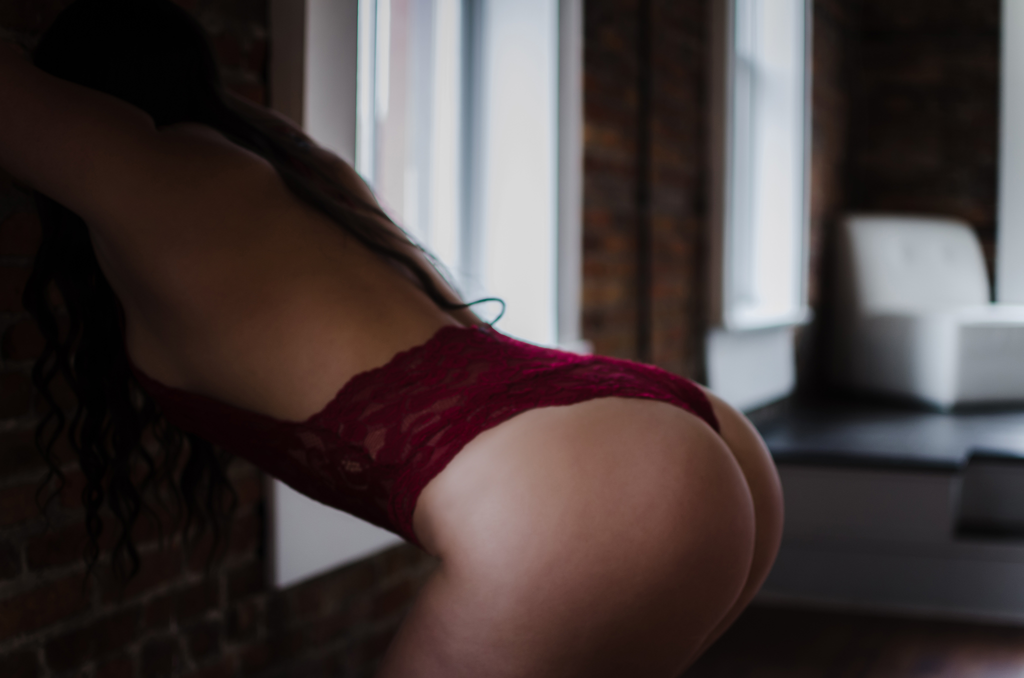 NC boudoir photography experience in belle vue wilmington venue with red lace bodysuit by Amandamarie Gillen Photography Wilmington NC photographer tushie tuesday pose