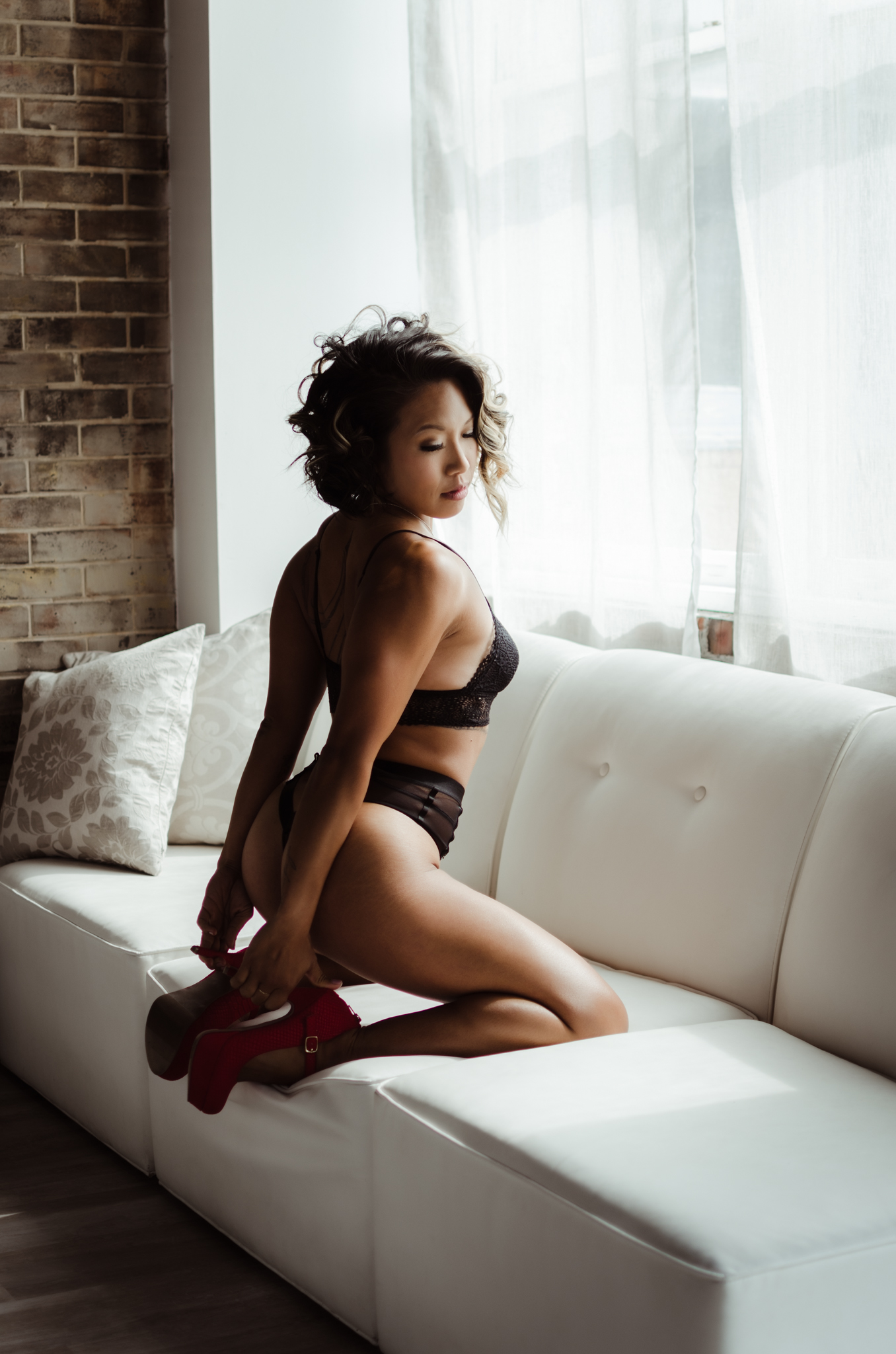 NC boudoir photography experience in belle vue wilmington venue with black lace lingerie by Victoria Secret by Amandamarie Gillen Photography Wilmington NC photographer tushie tuesday butt lifting pose on chair by window with natural light and red heels