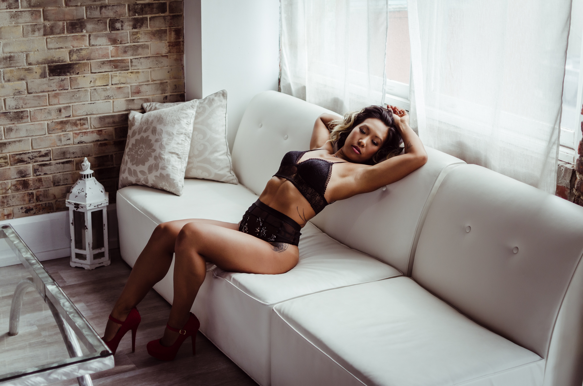 best NC boudoir photography experience in belle vue wilmington venue with black lace lingerie by Victoria Secret by Amandamarie Gillen Photography Wilmington NC photographer couch pose showing abs by window with natural light
