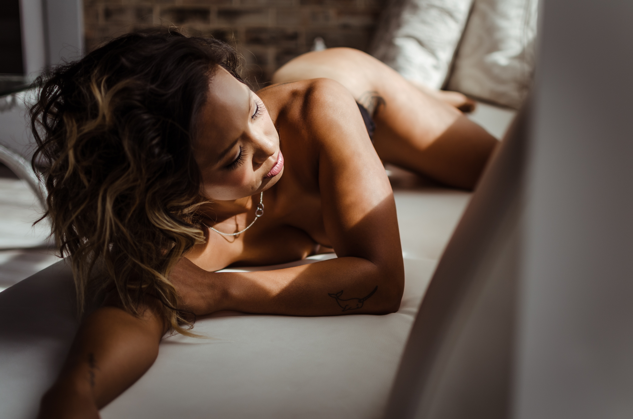 best NC boudoir photography experience in belle vue wilmington venue implied nude by Amandamarie Gillen Photography Wilmington NC photographer couch pose  by harsh window with natural light