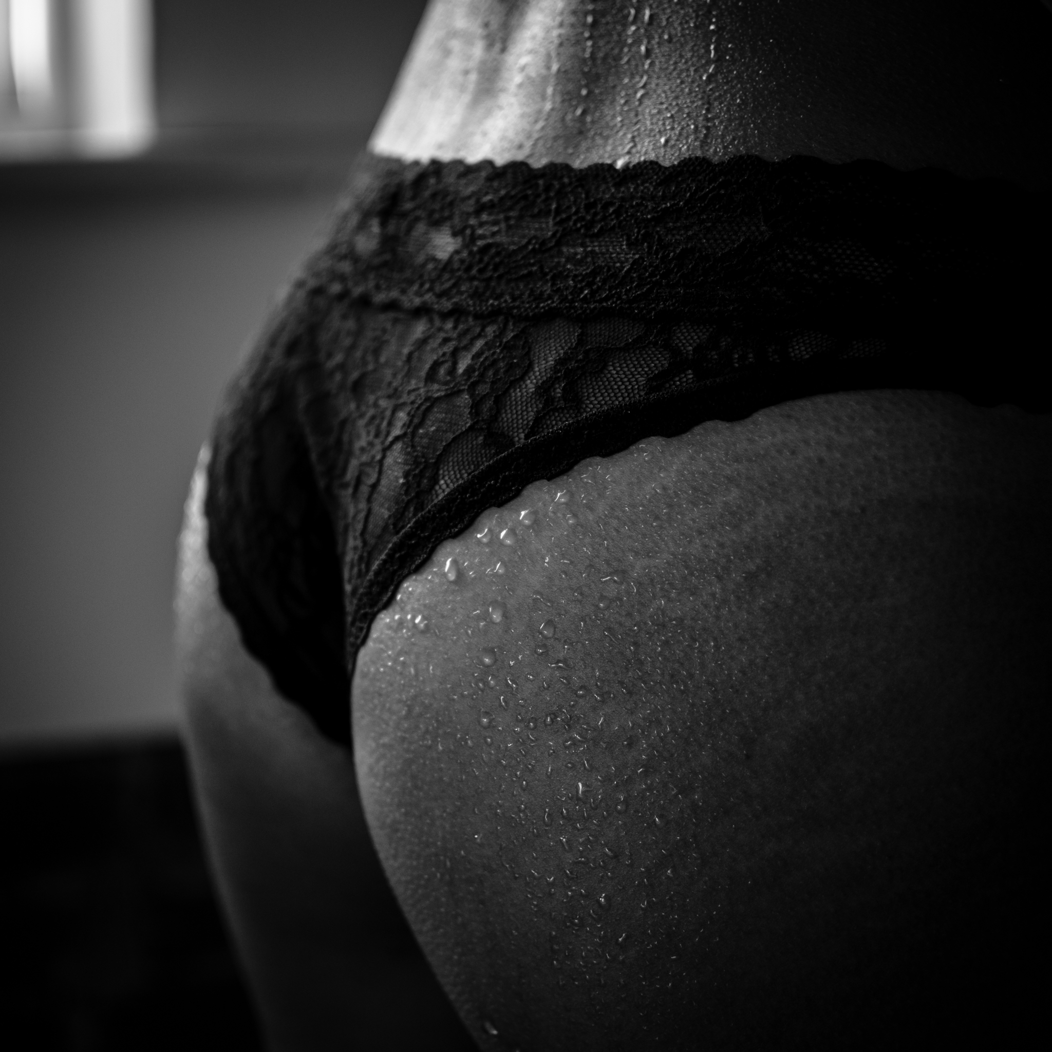 best NC boudoir photographer black and white portrait of butt tushietuesday by Amandamarie Gillen Photography Wilmington NC photographer standing wet pose showing water drops on skin by window with natural light