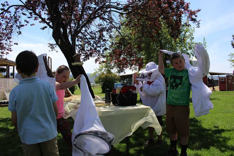 Students check out beekeeping equipment at one of the various stations set up on the Klann farm. Kids were invited to try on beekeeping suits.