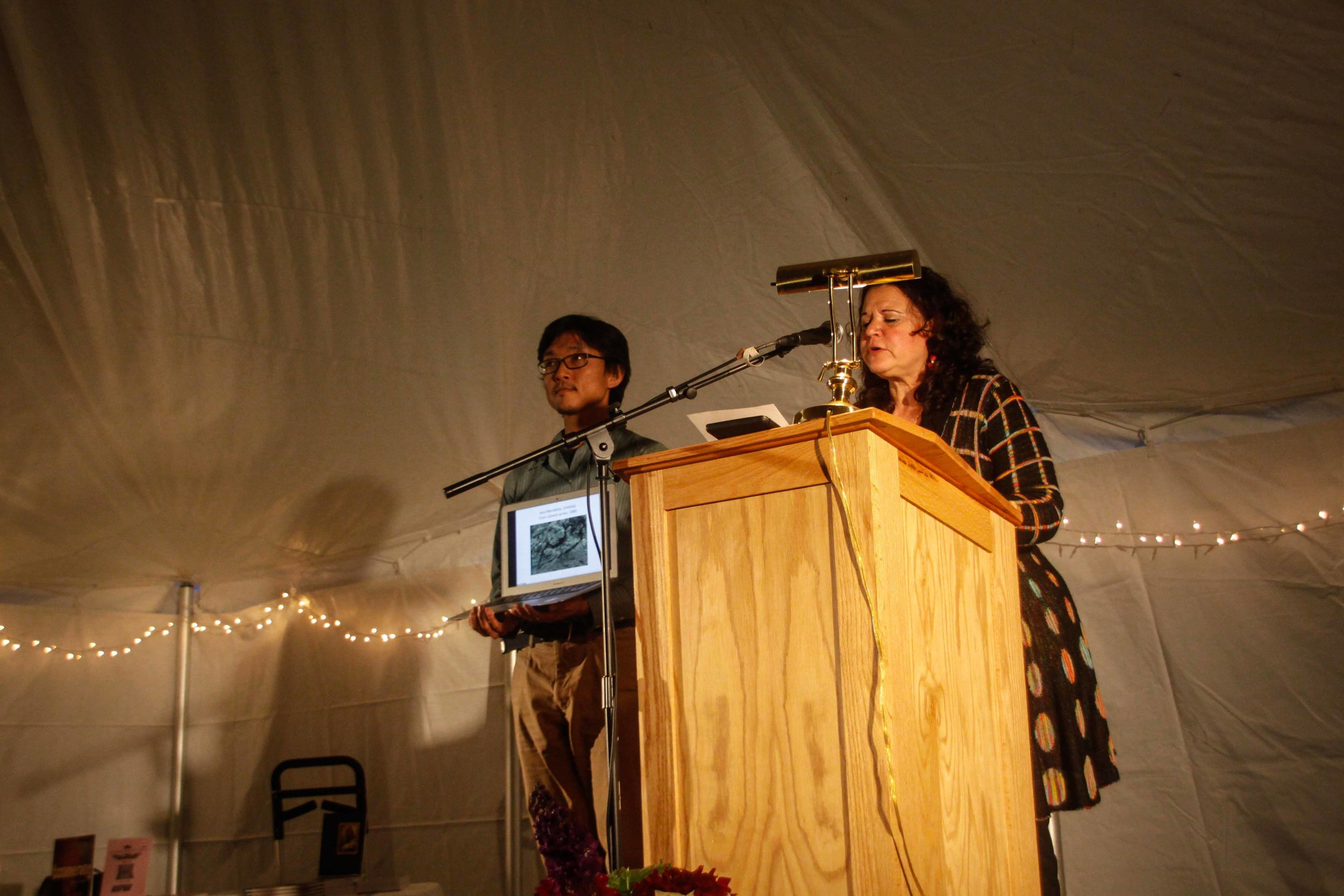 Brenda Cárdenas reads a poem while an audience member holds her computer to show the crowd a piece of artwork on which one of her poems is based. (Photo courtesy of  Justin Robert Cox)