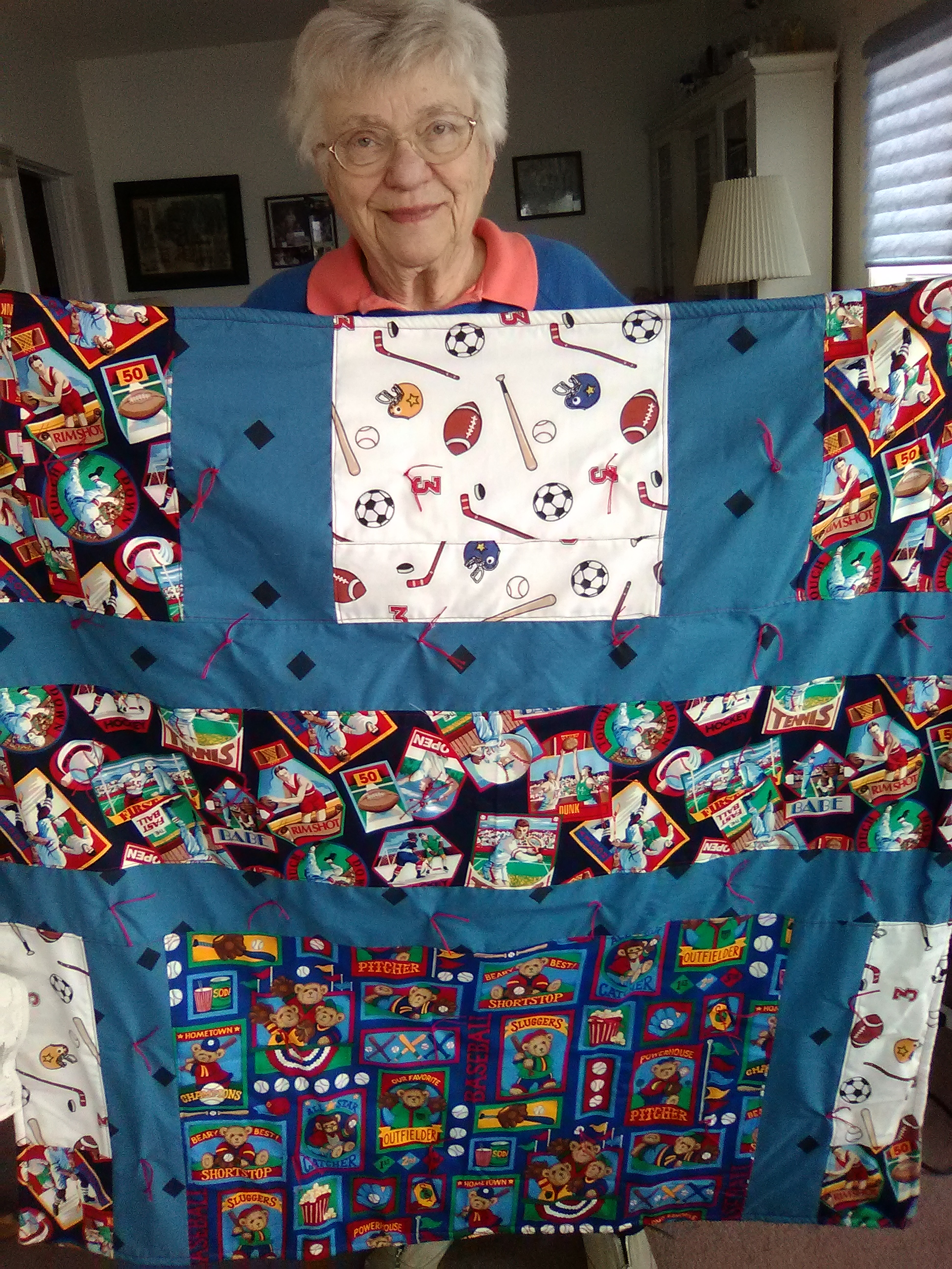 Above – Margaret Ebert with one of the many blankets she has made for use in care centers! Thank you!