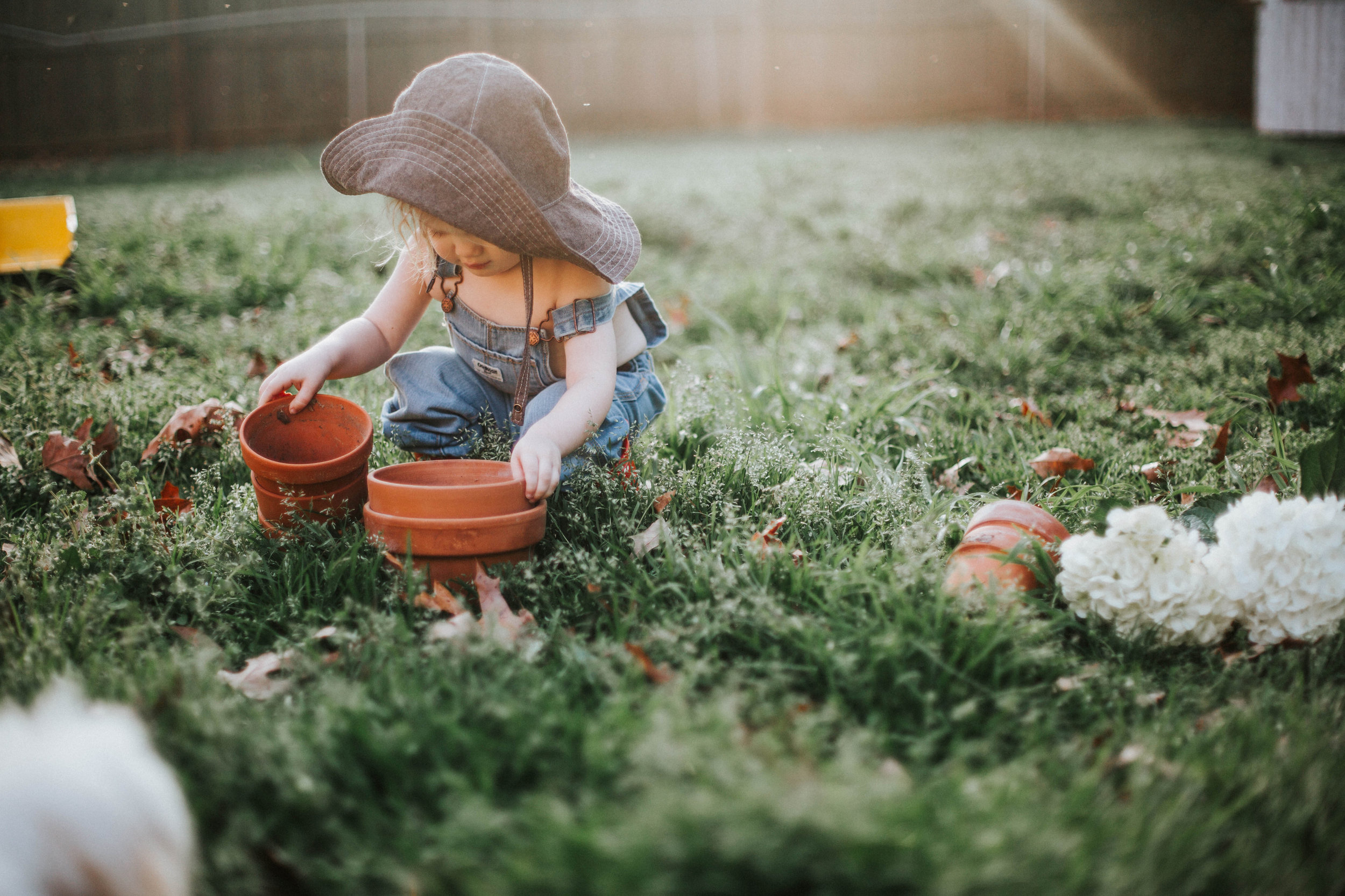 Toddler in garden with wide brim sun hat by Bluecorduroy.com