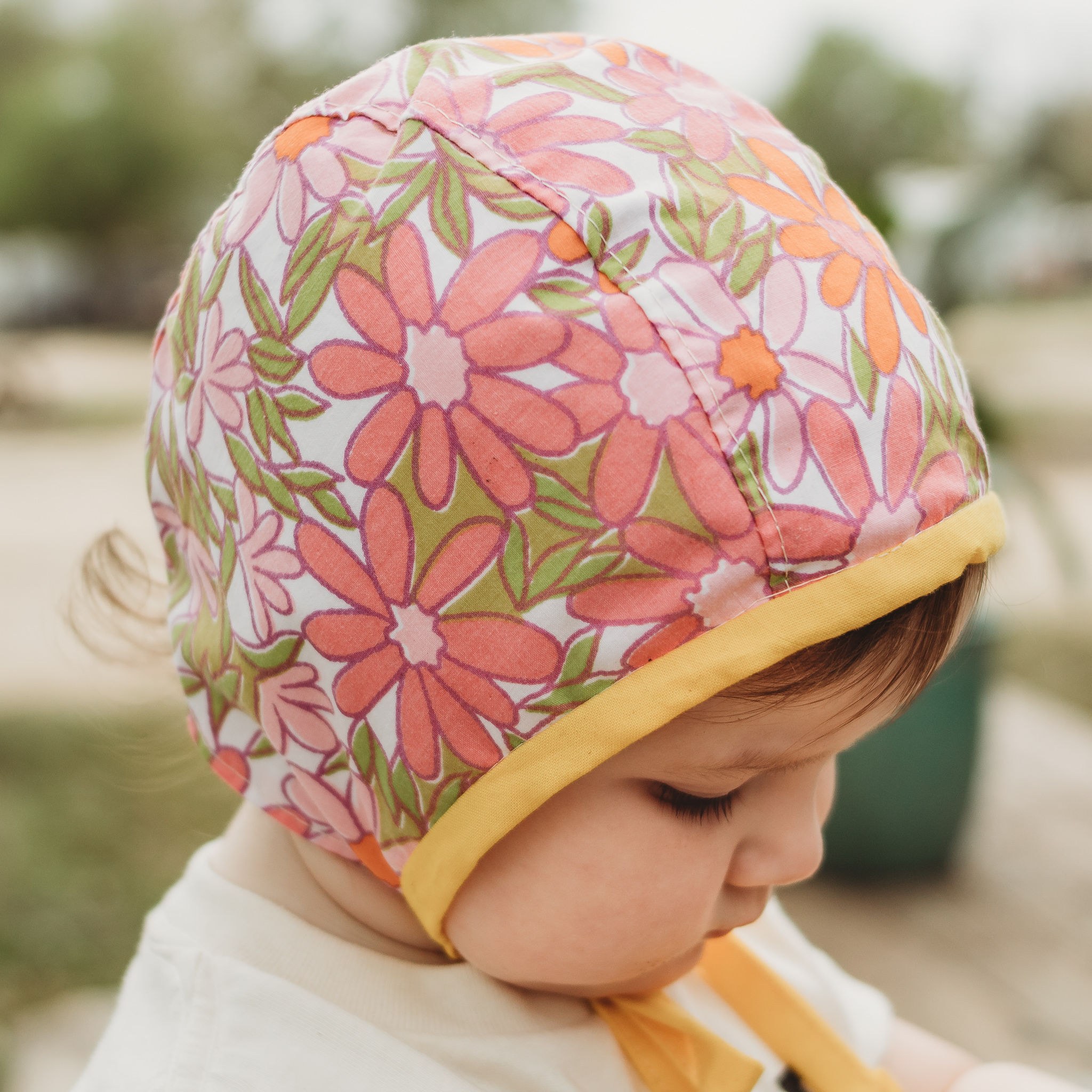 Baby bonnet for spring with retro pink flower fabric by Blue Corduroy