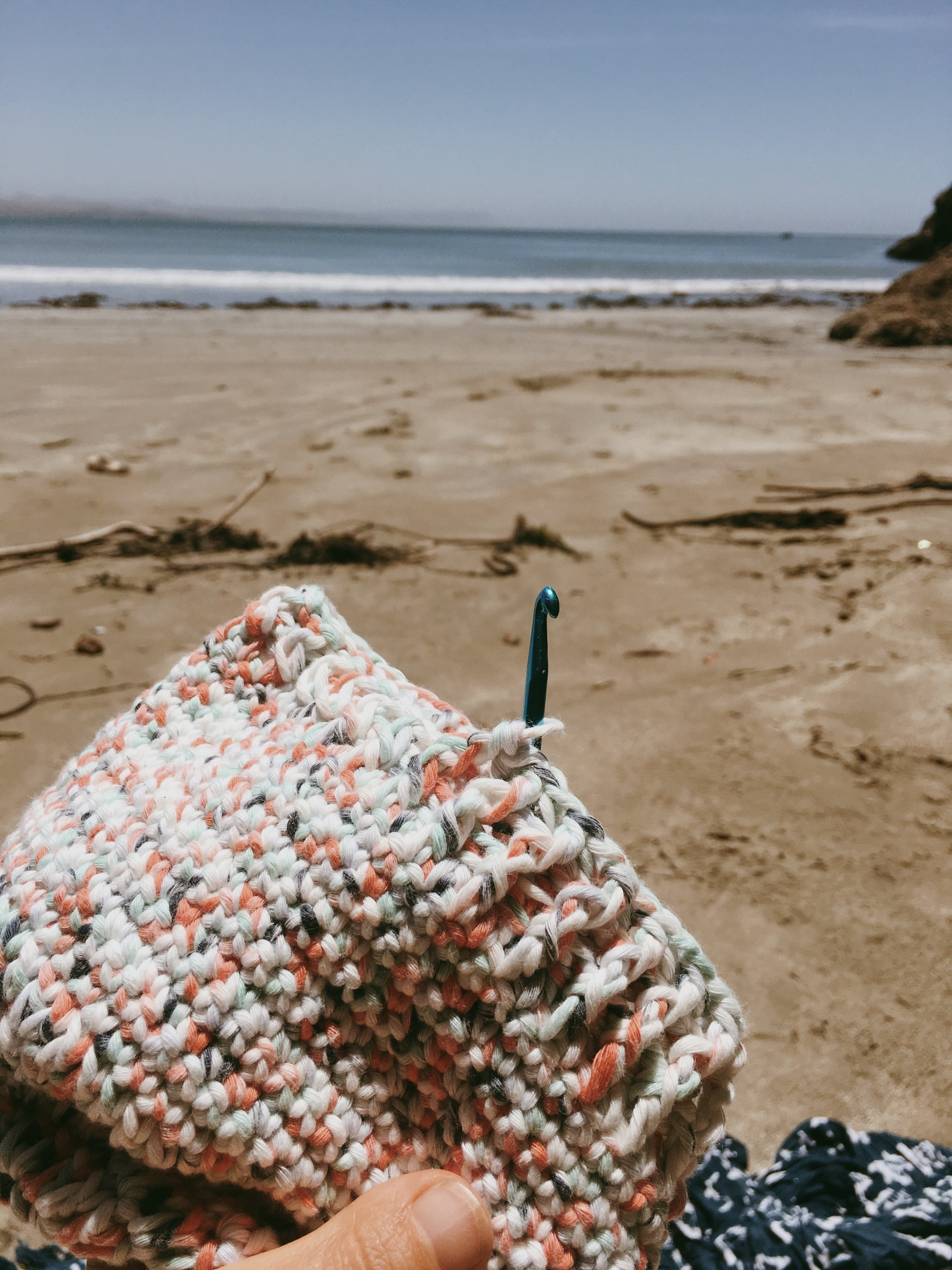 Crocheting a baby bonnet at the beach