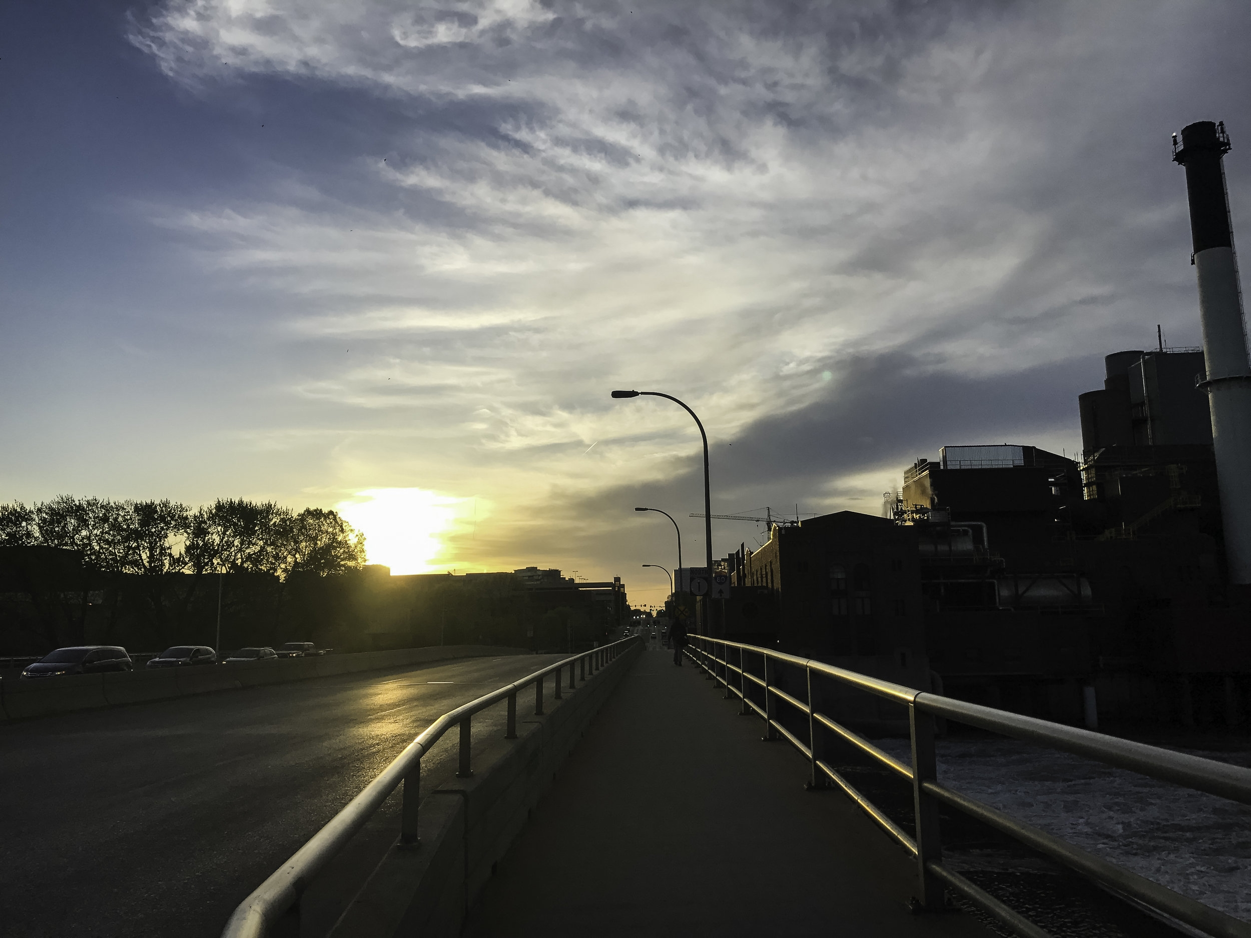 Image Description: Early morning, the sun is rising, over a paved walking path next to a road. There is no traffic and no cars coming. Iowa City, Iowa.