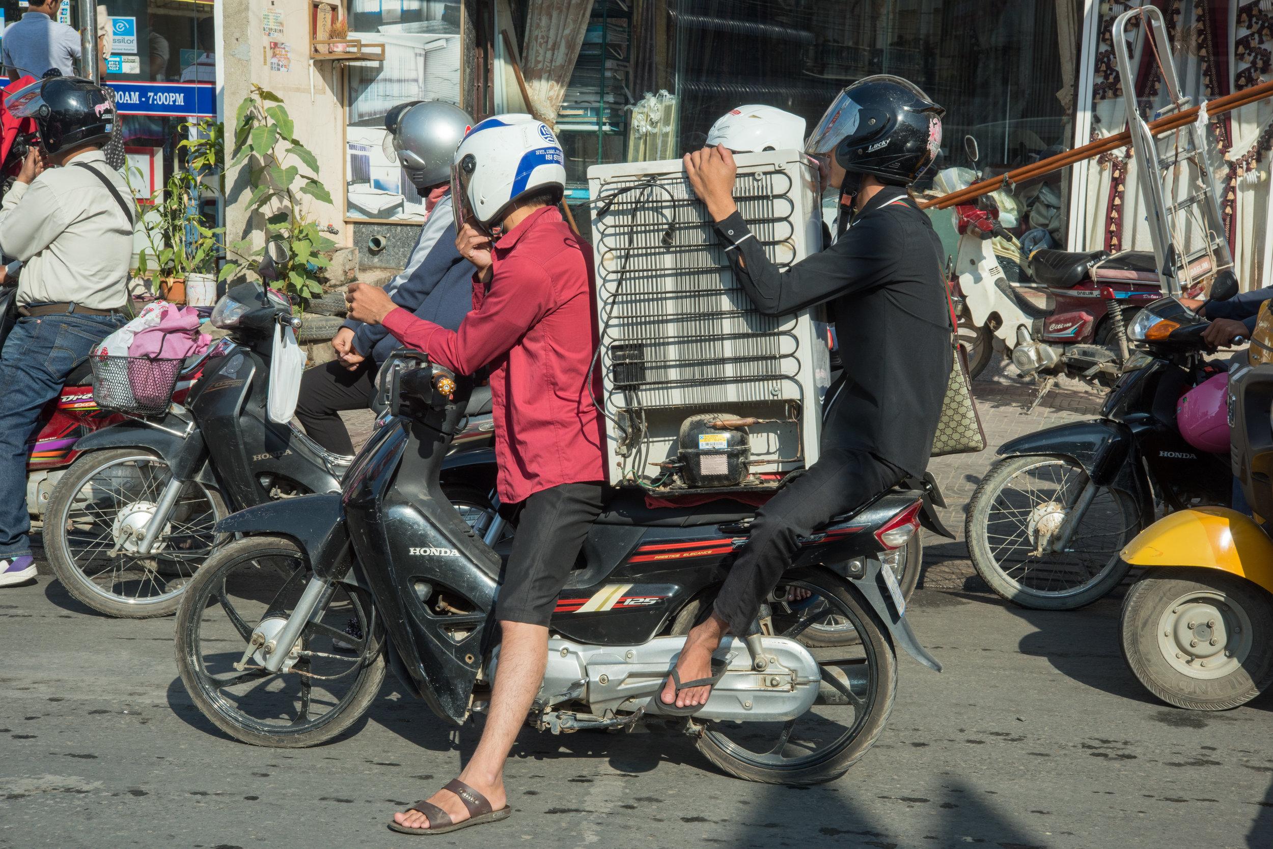 Motorbike transporting bar fridge, Phnom Penh, Cambodia
