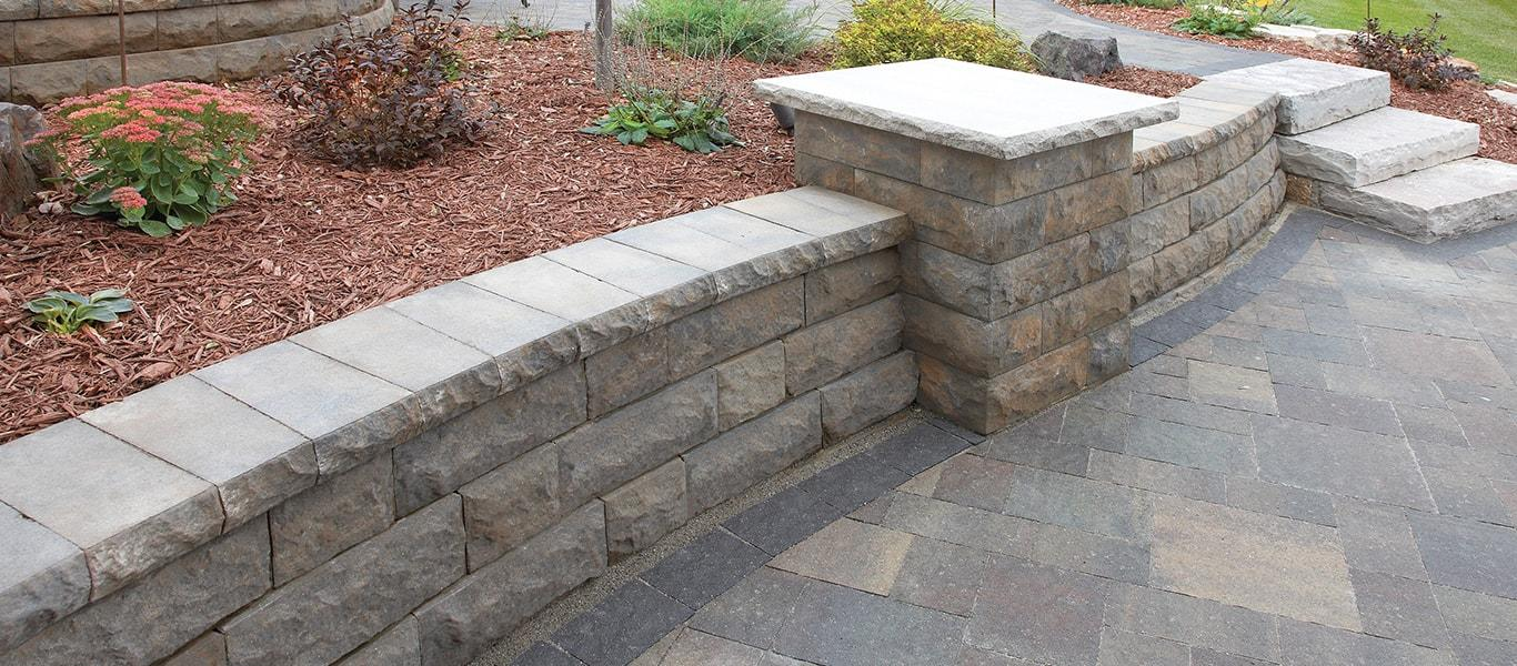 Retaining wall with Belgard Pavers, complemented by mulch landscaping