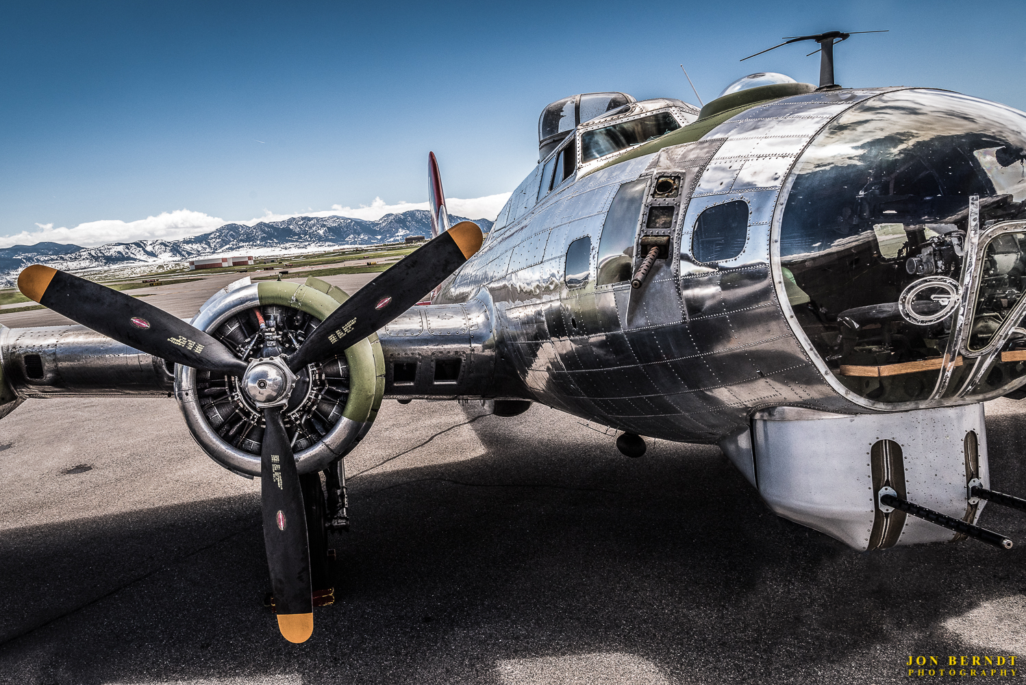 """B-17G """"Madras Maiden"""". This photograph is perhaps my personal favorite of the set. I put the camera on an extended tripod and lift it up, with the shutter set to timer. I had to make quite a number of these exposures before I got one that was right! The """"chrome"""" look in this image is slightly exaggerated, but the intention was to produce a stylized photograph that emphasized the reflections in the aircraft skin. I also wanted to be up close and personal to the cockpit, and this was about the best I could do under the circumstances.   Click here  for information on purchasing a copy of this print."""