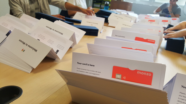 Monzo's coral-pink cards being packed. Photo: Monzo.