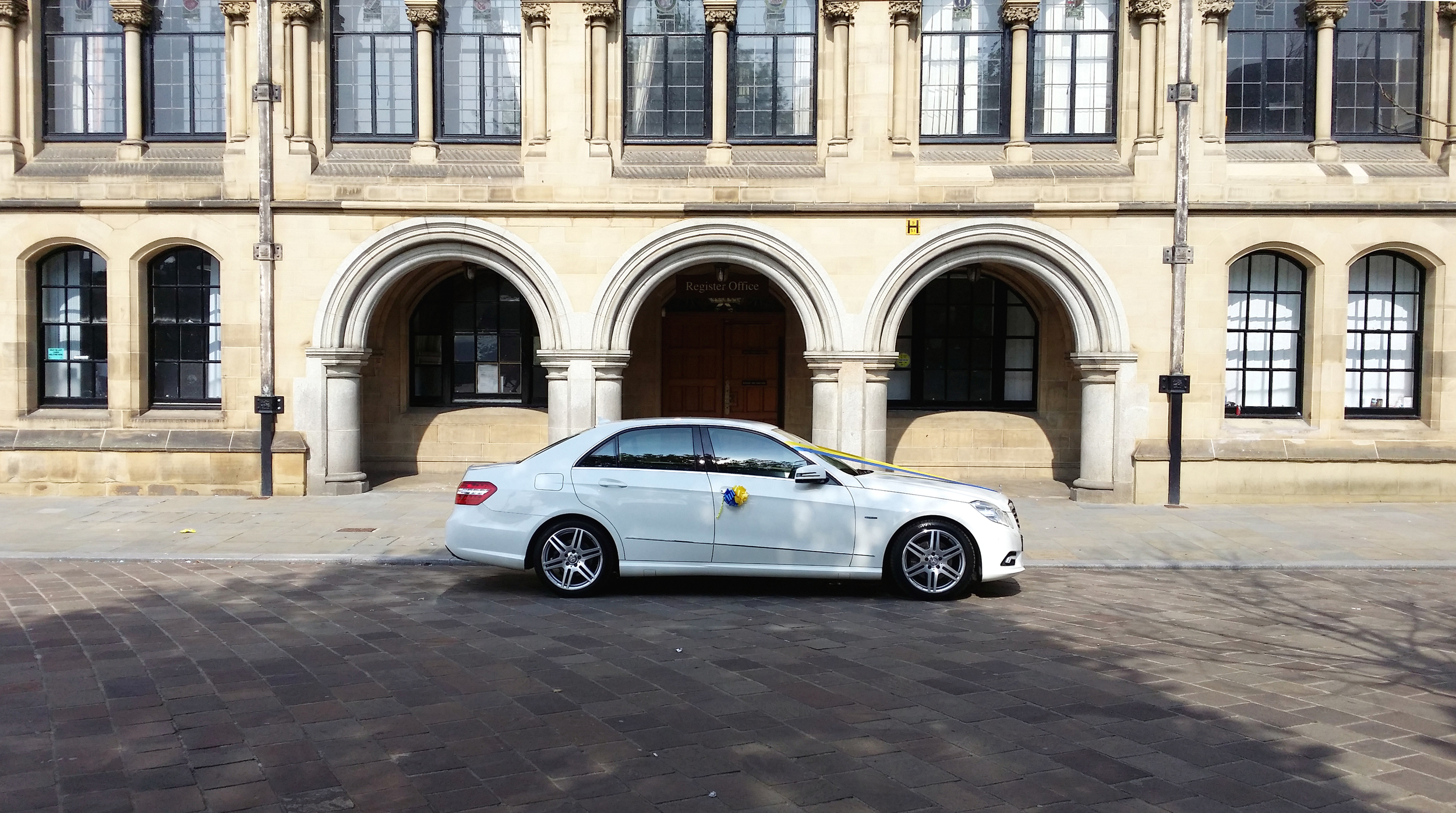 White Mercedes wedding car parked in front of Bradford City Hall archways