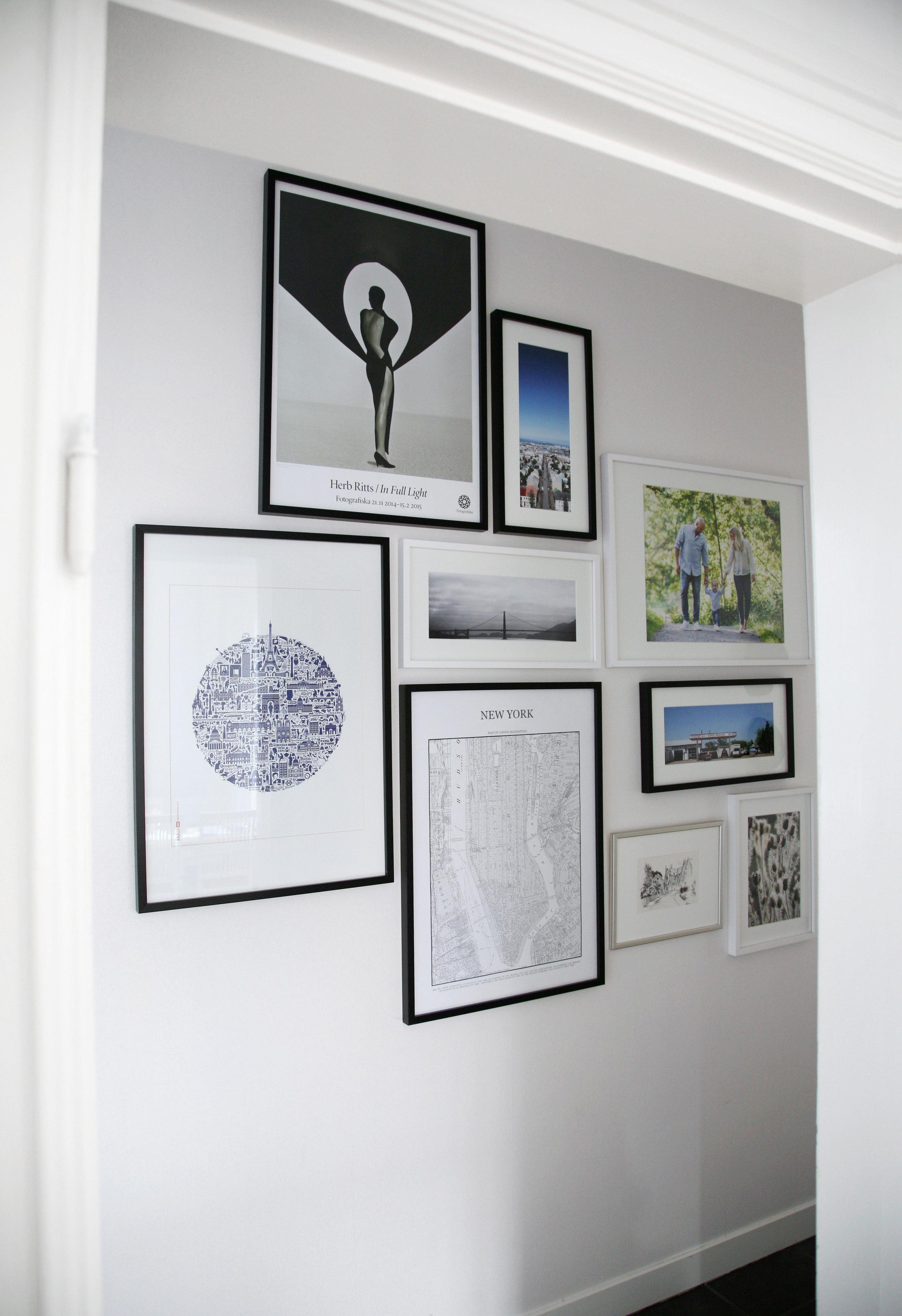 Här är en bild från vår serveringsgång. Att blanda några olika storlekar, former och färger på ramarna ger liv åt tavelväggen. Här har vi allt från reseminnen och illustrationer till fotografier och en blyertsteckning. När du ska planera din tavelvägg ta god tid på dig innan du börjar spika.Pussla gärna med dina bilder på golvet eller klipp papper till det format tavlorna är i och tejpa upp på väggen för att få en känsla av hur det kommer se ut. Och, använd vattenpass! Foto: Johanna Walden