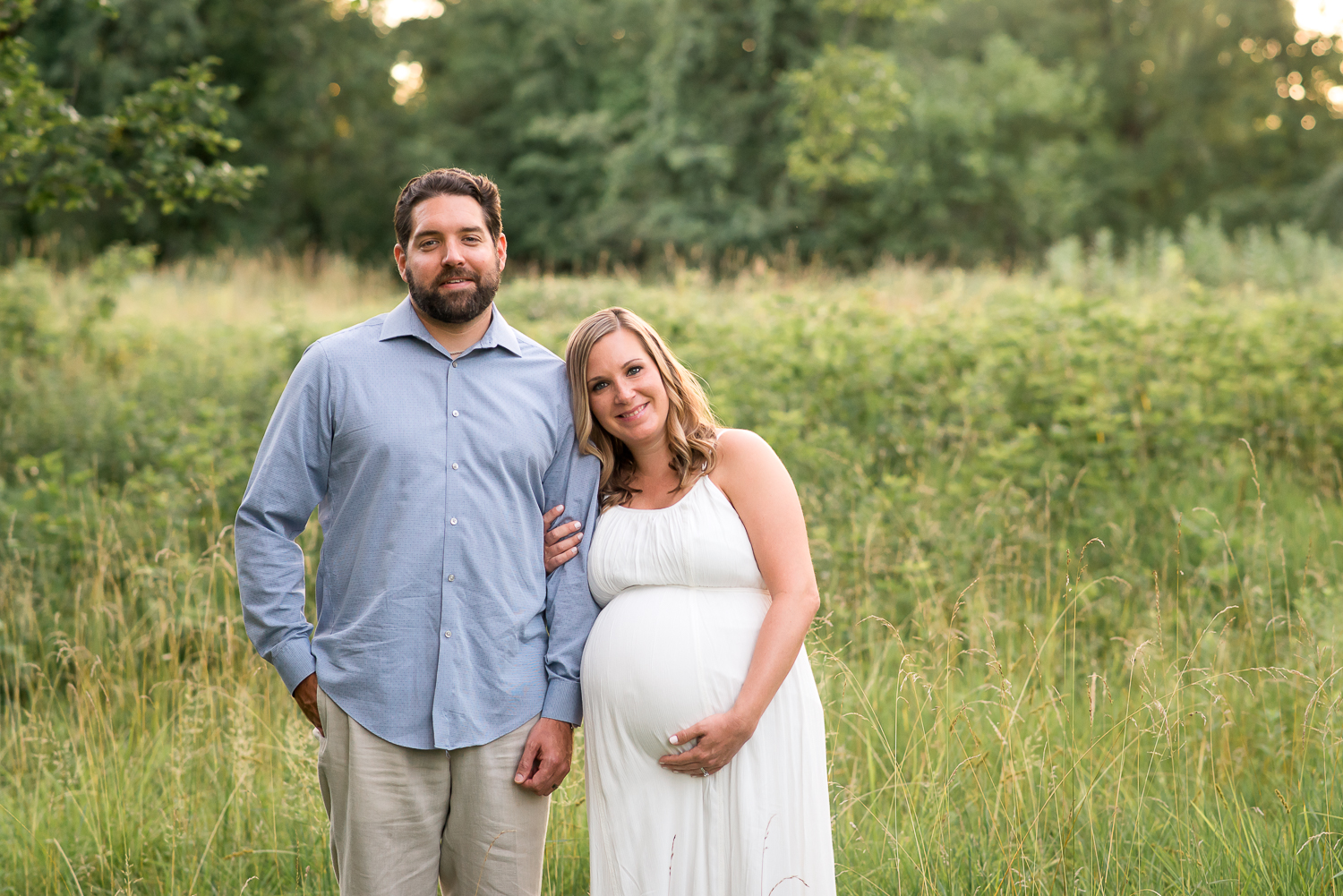 maternity photography pregnant woman in long white dress with husband in tall grasses Baltimore Photographer
