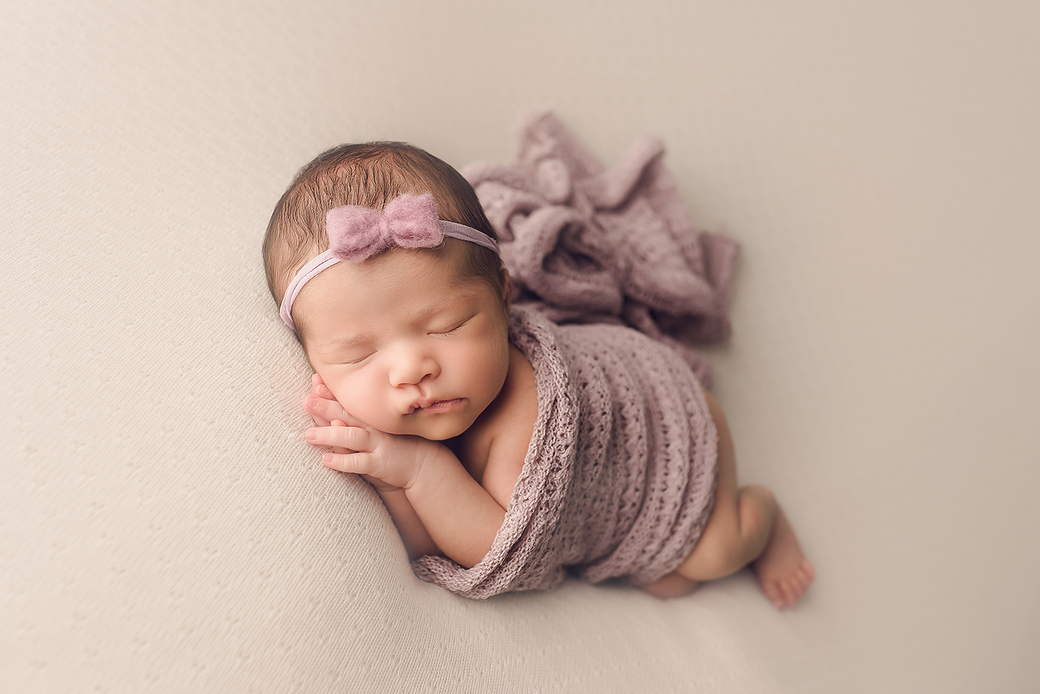 Baltimore Maryland Newborn Photographer Jessica Fenfert baby girl on cream purple wrap sidelying