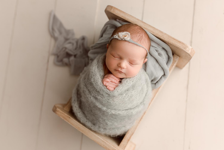 Baltimore Maryland Newborn Photographer Jessica Fenfert baby girl in gray in bed