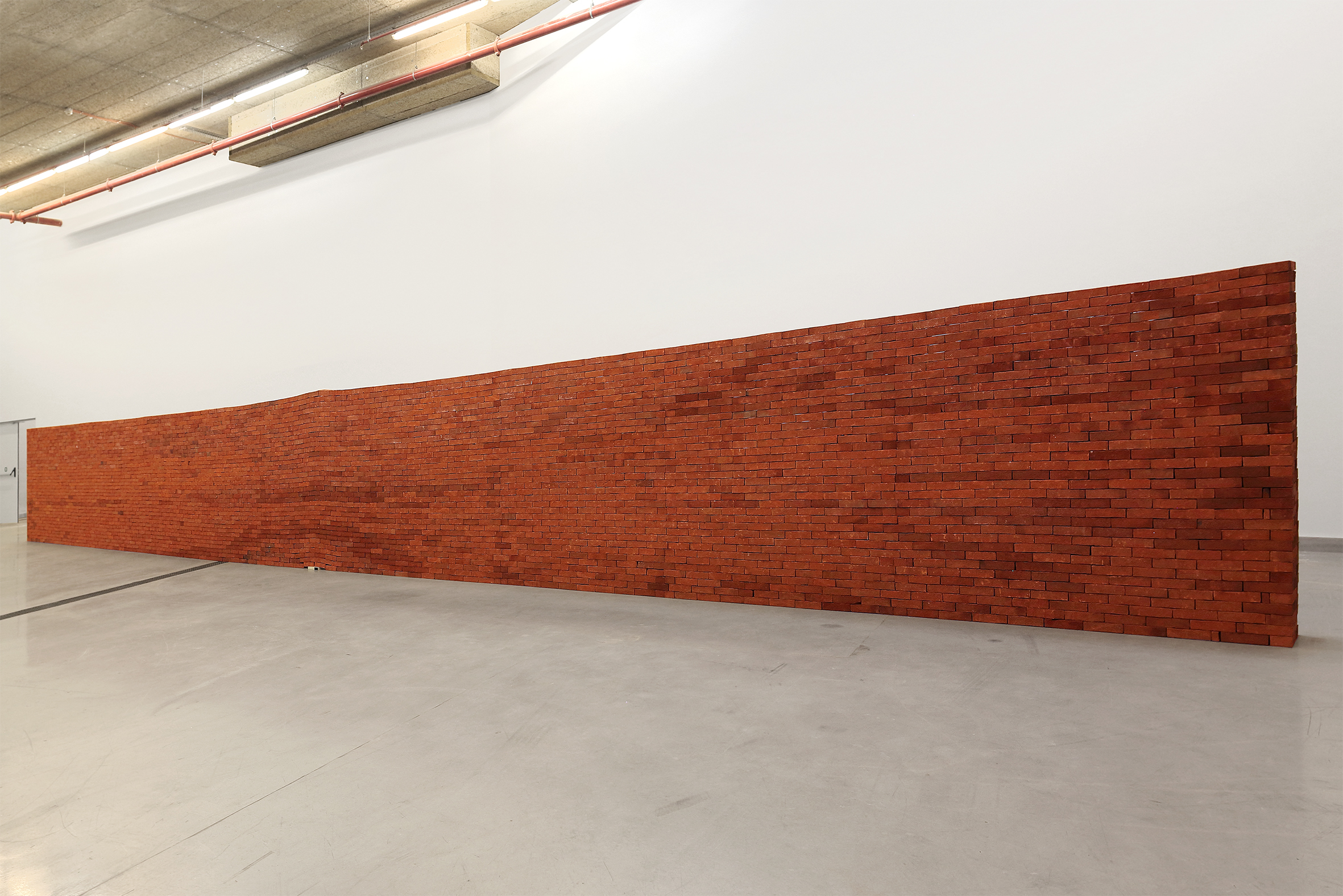 El castillo   /   The Castle  , 2007  Ladrillos, edición de  El castillo  de Franz Kafka / Bricks, edition of Franz Kafka's  The Castle   2300 x 175 x 40 cm  Vista de la instalación en la exposición After Babel, Annex M, Athens, 2018 / Installation view at the exhibition After Babel, Annex M, Athens, 2018