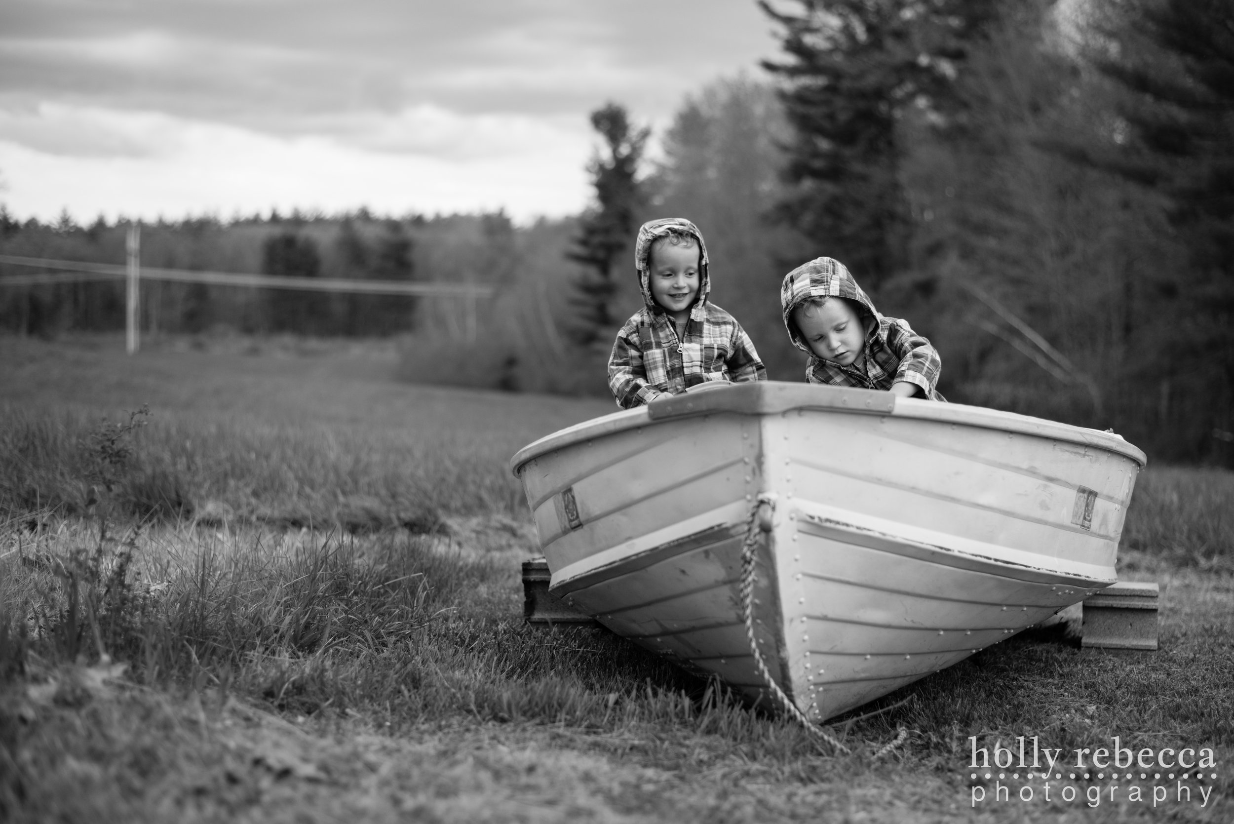 Twin boys playing in a boat by the New Hampshire woods