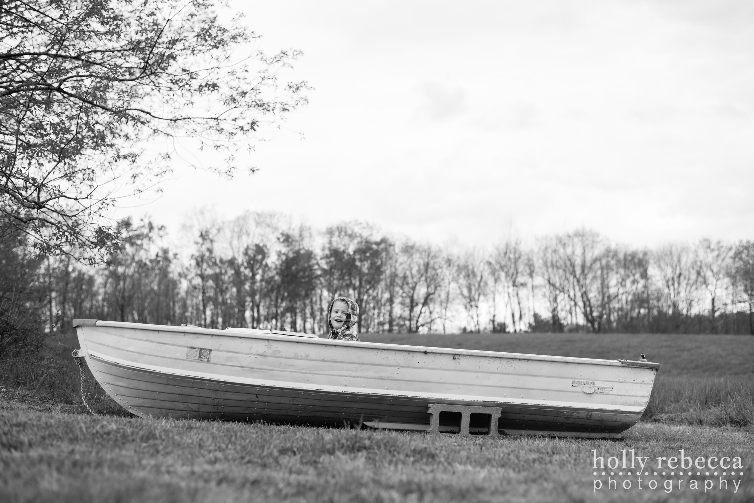 Boy playing in a boat by the New Hampshire woods