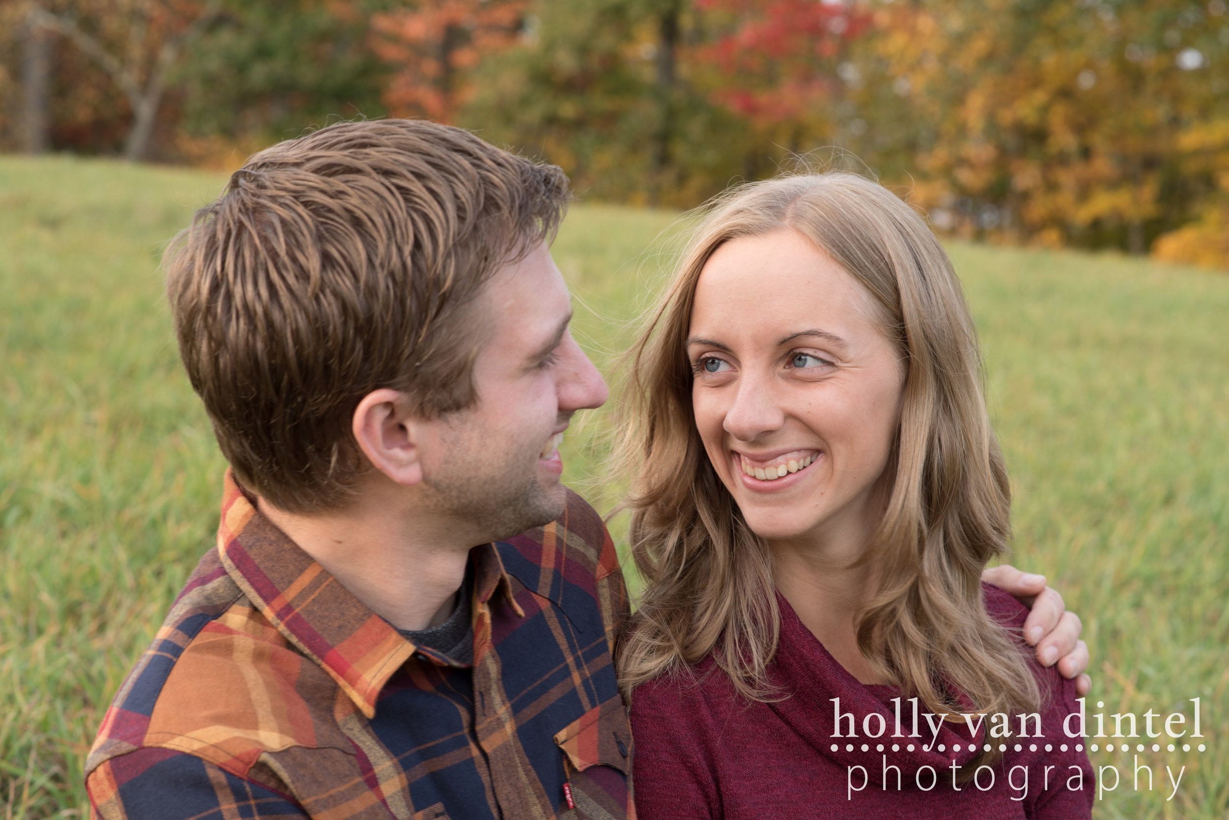 Engaged couple sitting in field