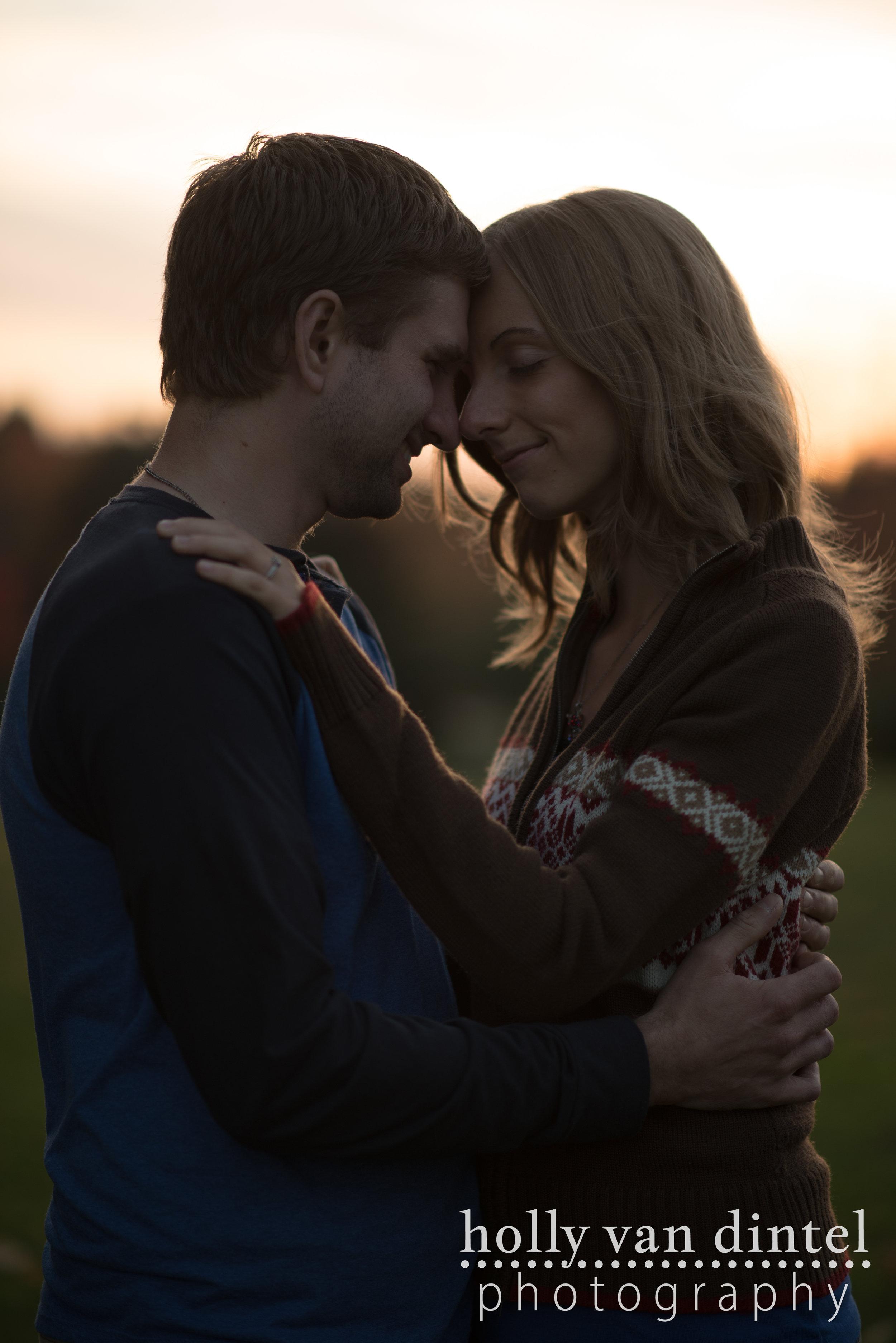 Backlit sunset image of engagement couple, foreheads together embracing