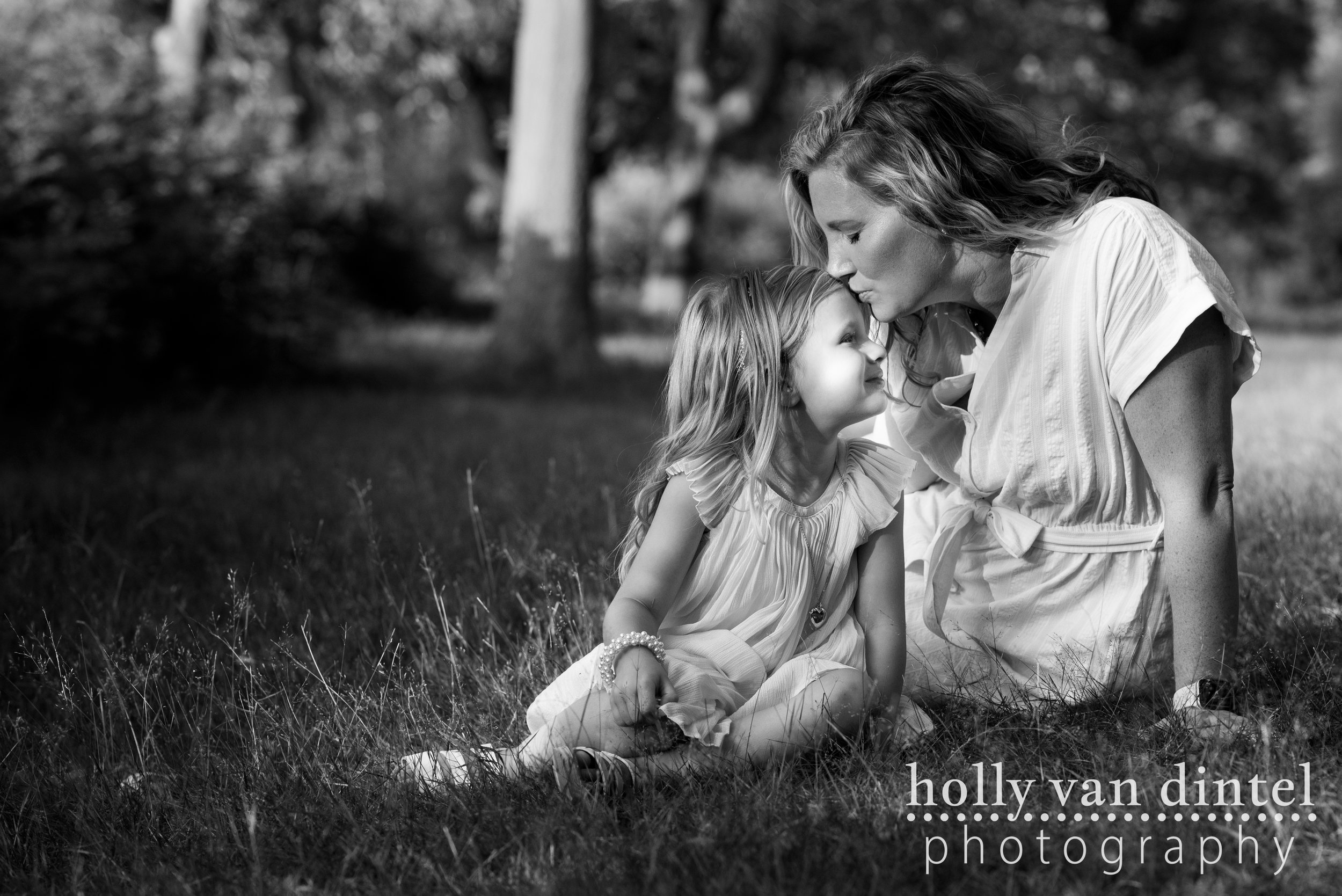 Black and white image of a mother kissing little girl on the forehead