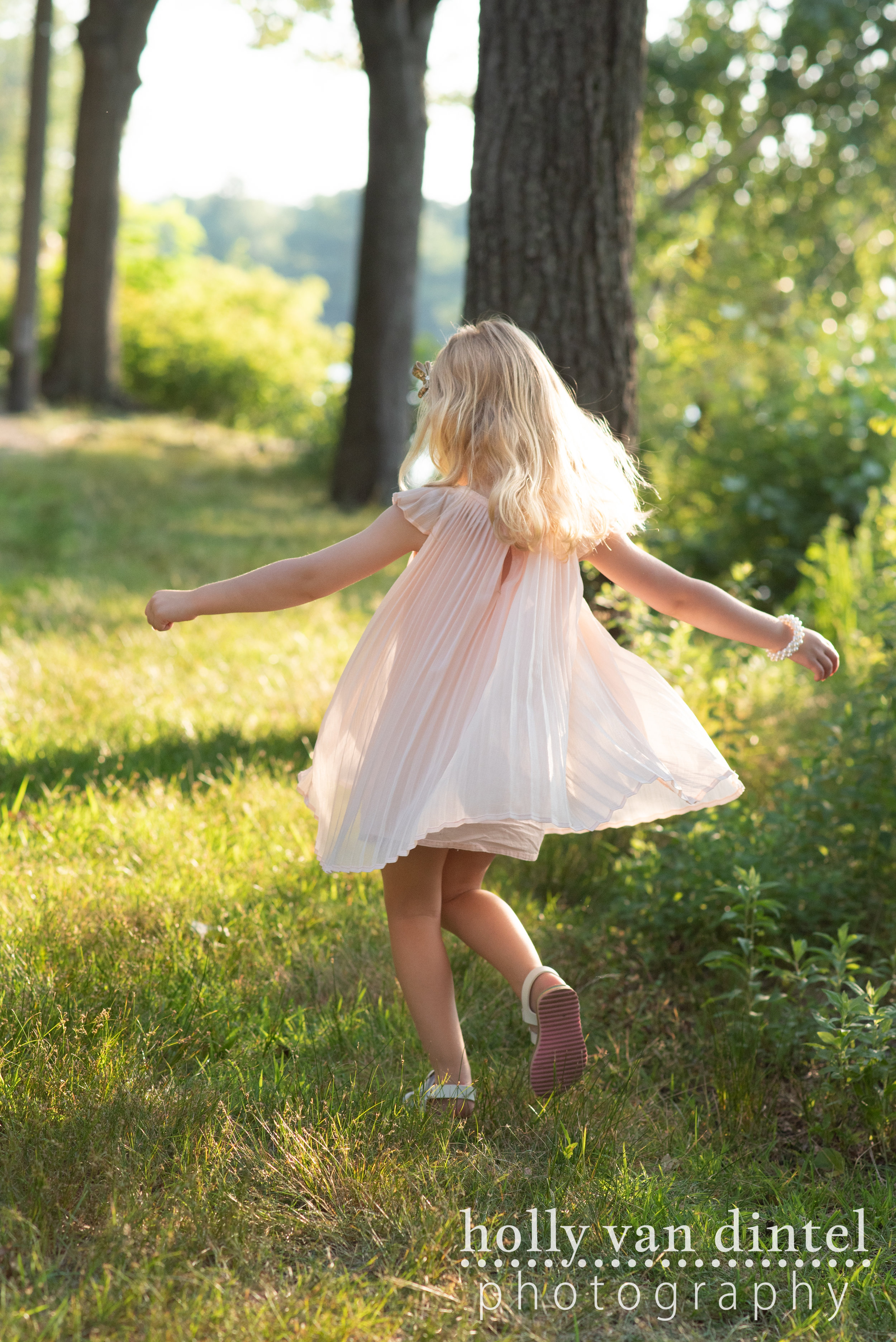 Little girl wearing a pink dress and twirling in the sunshine.