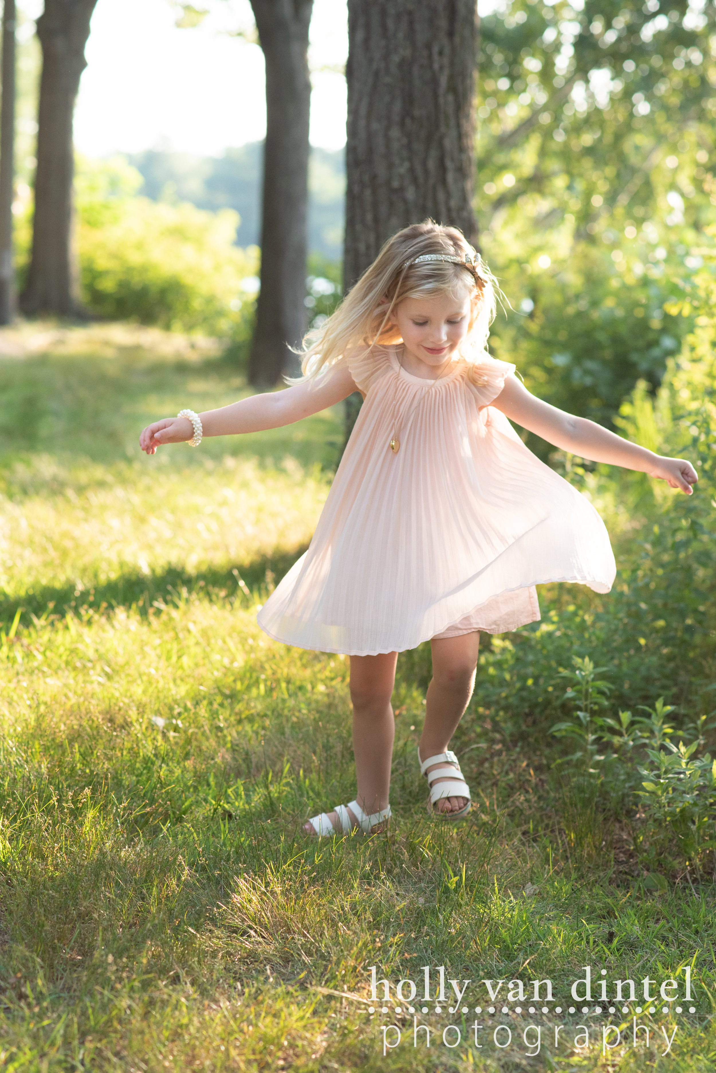 Little girl wearing pink dress and spinning in the sunshine