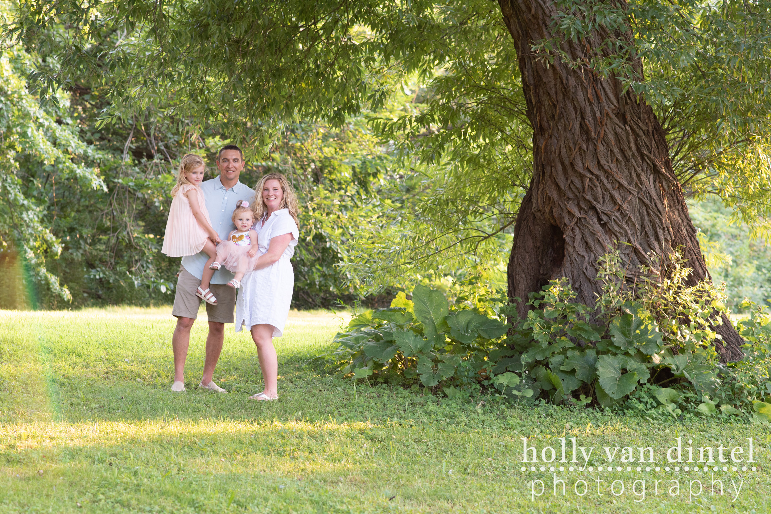 Family with two little girls standing together under a large tree in a park.