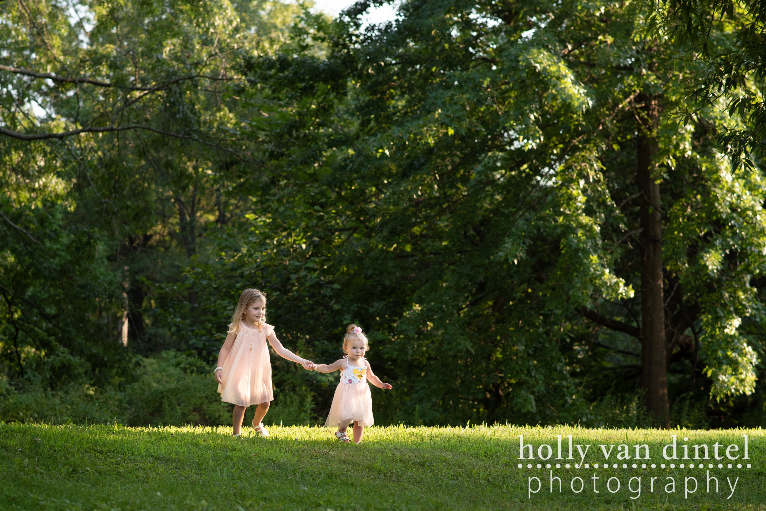 Two little girls holding hands and running through the grass at a park.