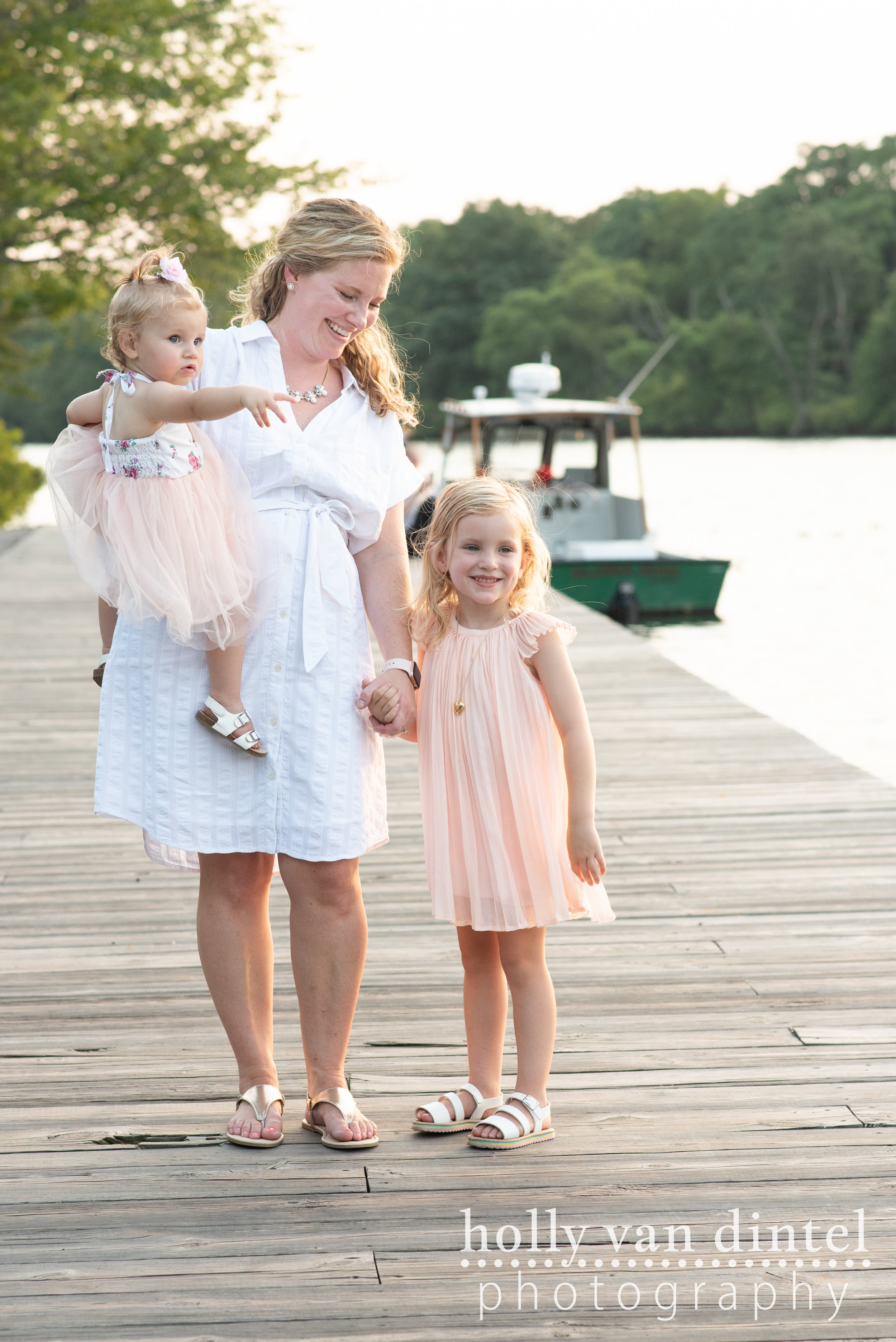 Mother with too little daughters standing on dock by river.