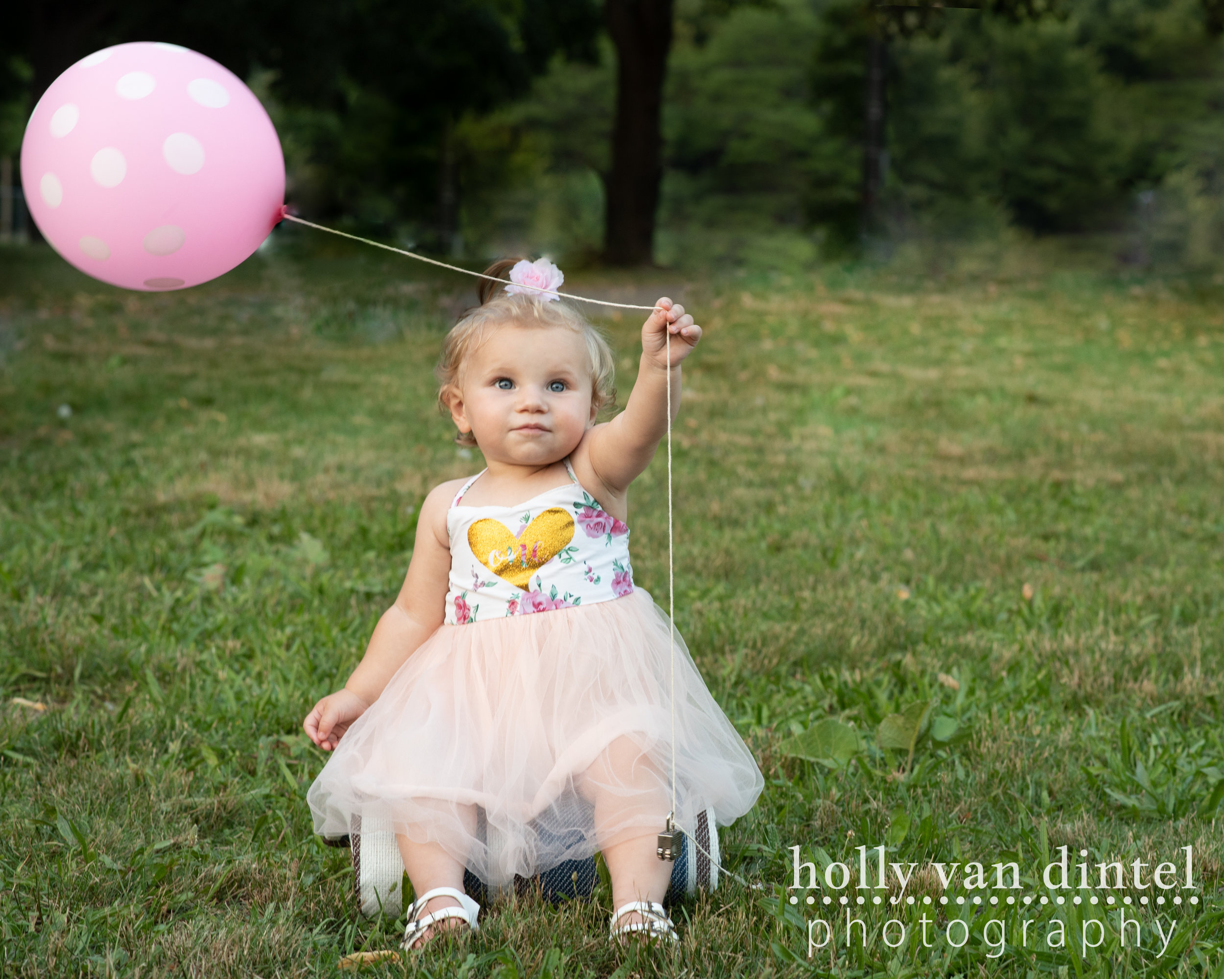 Little girl first birthday with balloon sitting in grass.