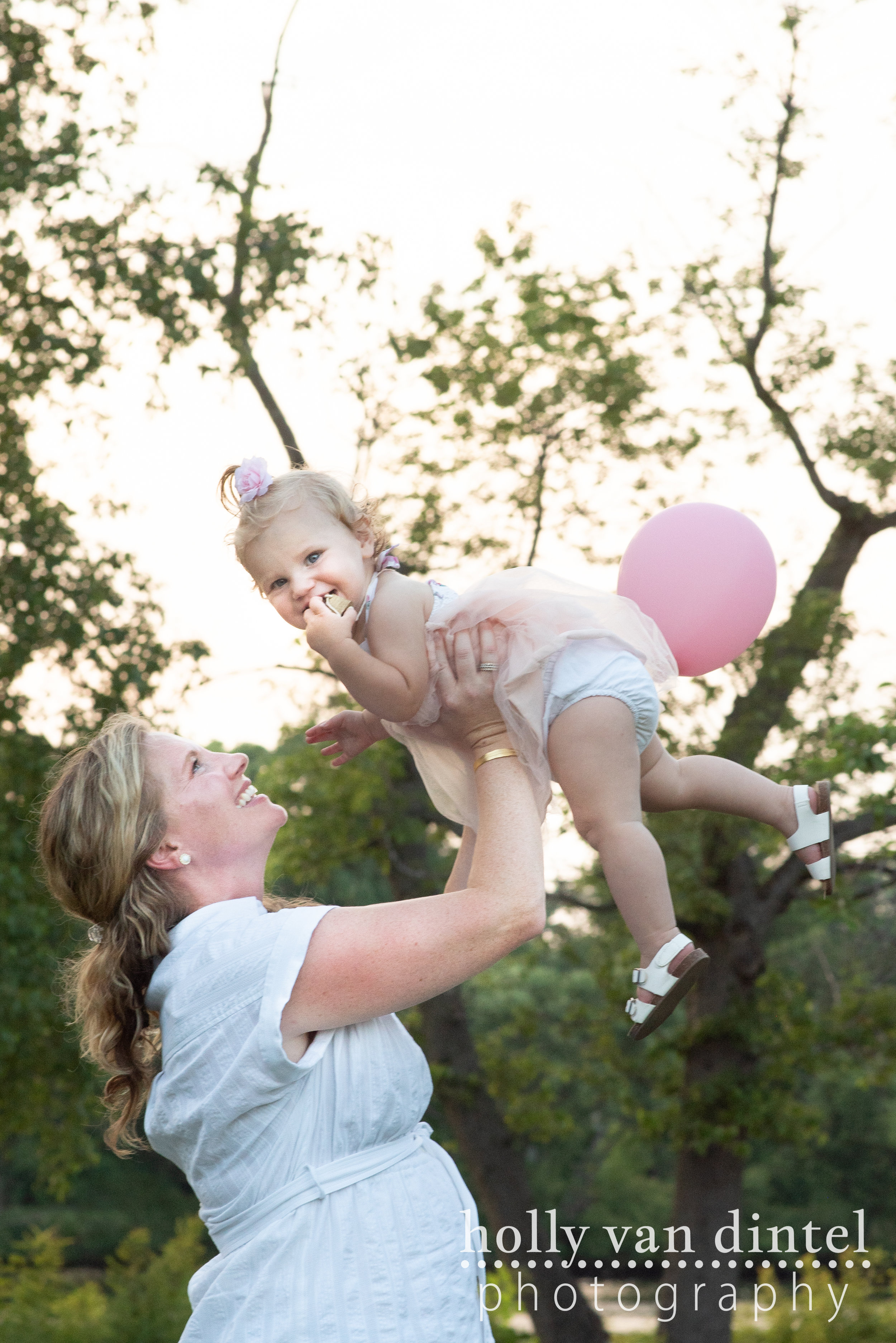 Mother holding little girl with balloon for first birthday.