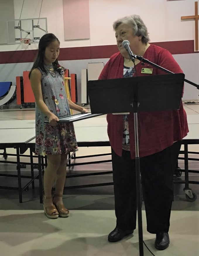 Virginia Flo, Regional Director of Minnesota for Lutherans For Life, presents Millie with the 2019 Lutherans for Life Essay Award at her 8th-grade graduation.