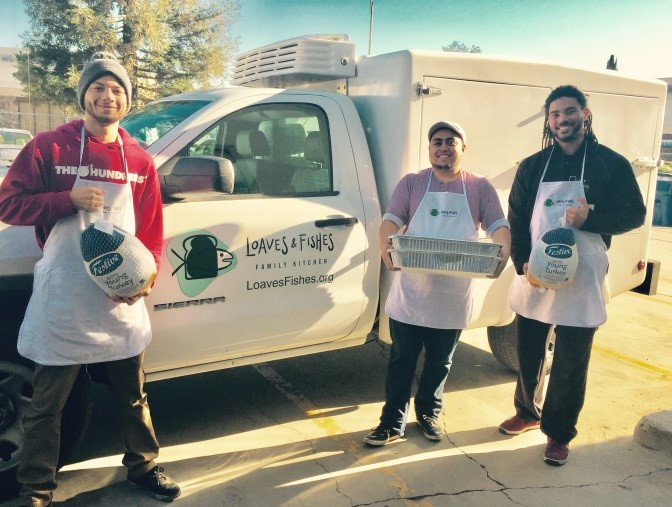 Loaves & Fishes' team (Evan, Marco and Randy) load the truck todeliver turkeys and meals to our partners.