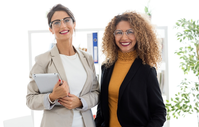 Two beautiful young businesswoman posing in the office.