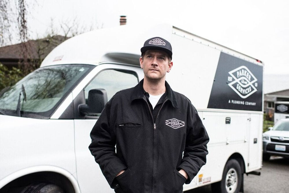 Nate Parker, of Parker Services looks pretty good in his signature jacket and hat, in front of their custom van.
