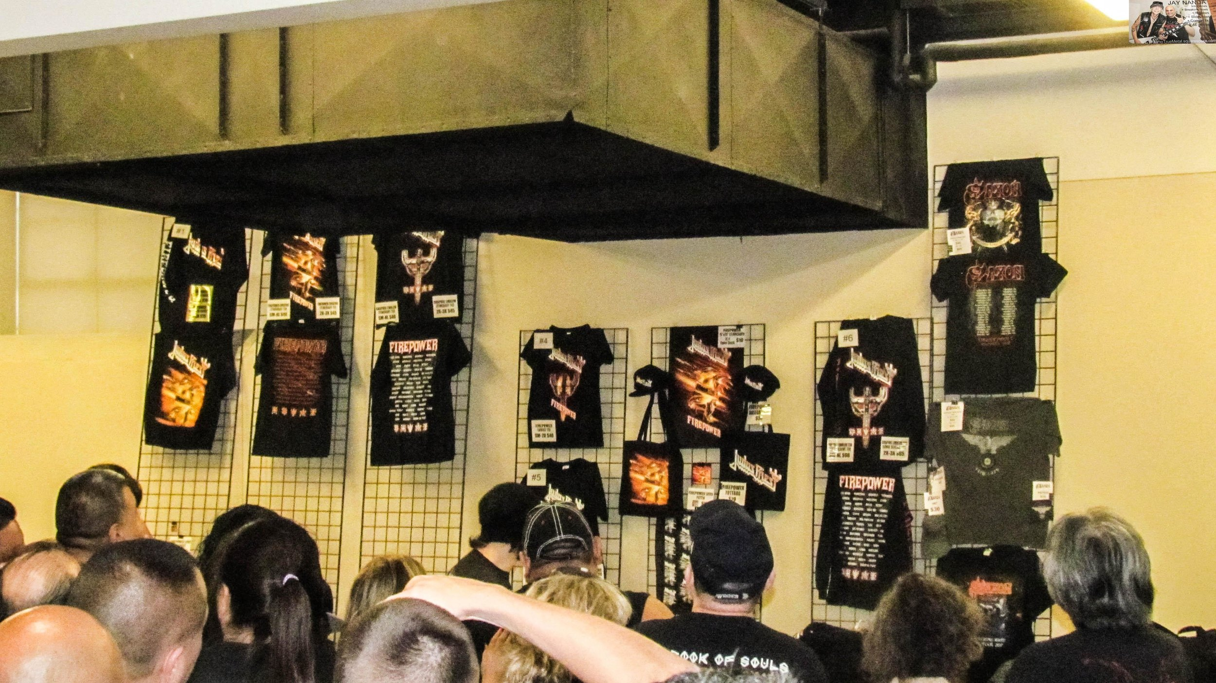 The merch booth displays Judas Priest and Saxon T-shirts.